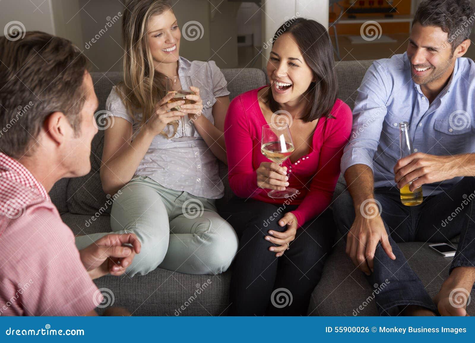 Grupp av vänner som sitter på Sofa Talking And Drinking Wine