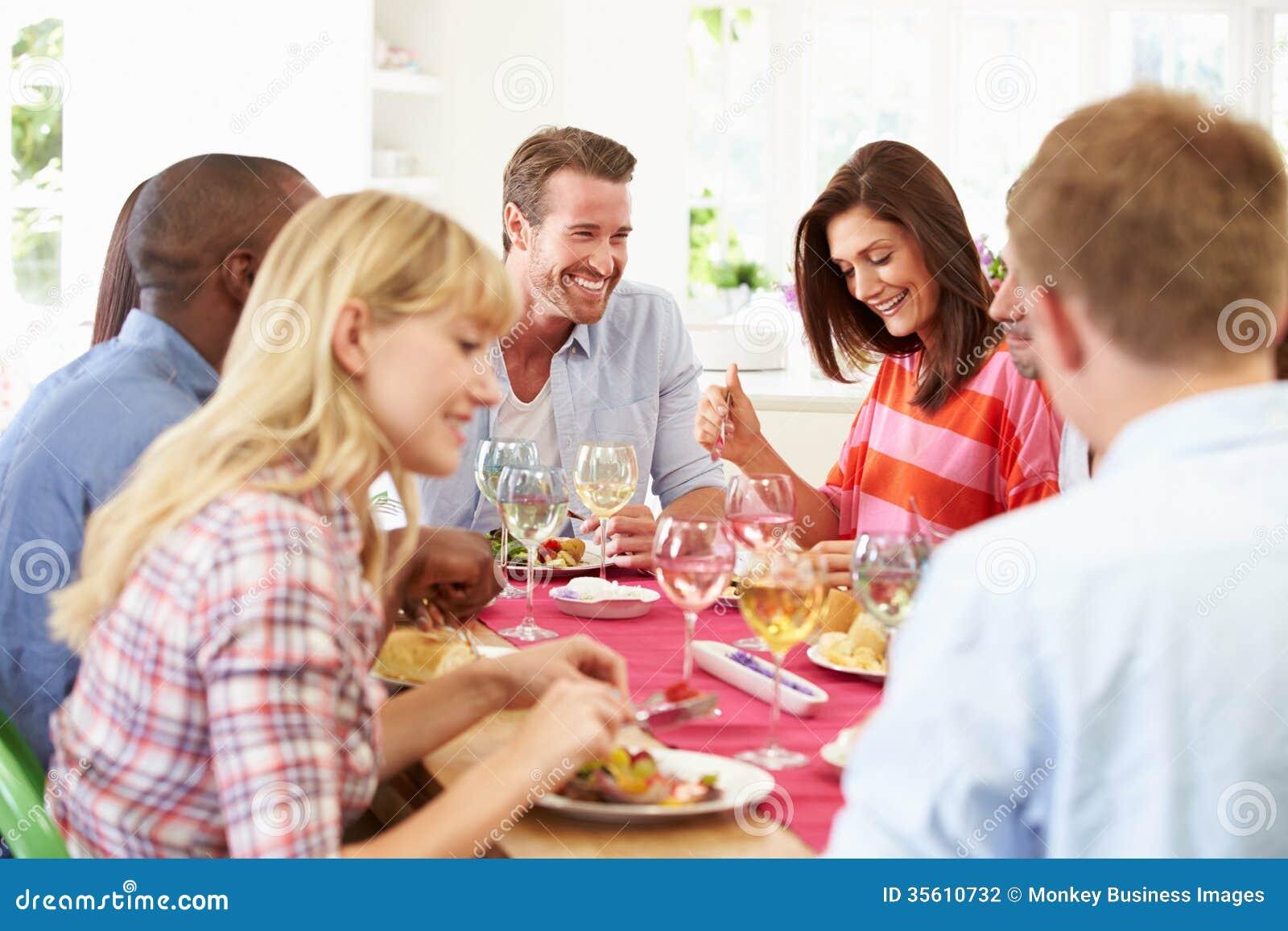 Grupp av vänner som sitter runt om tabellen som har matställepartiet