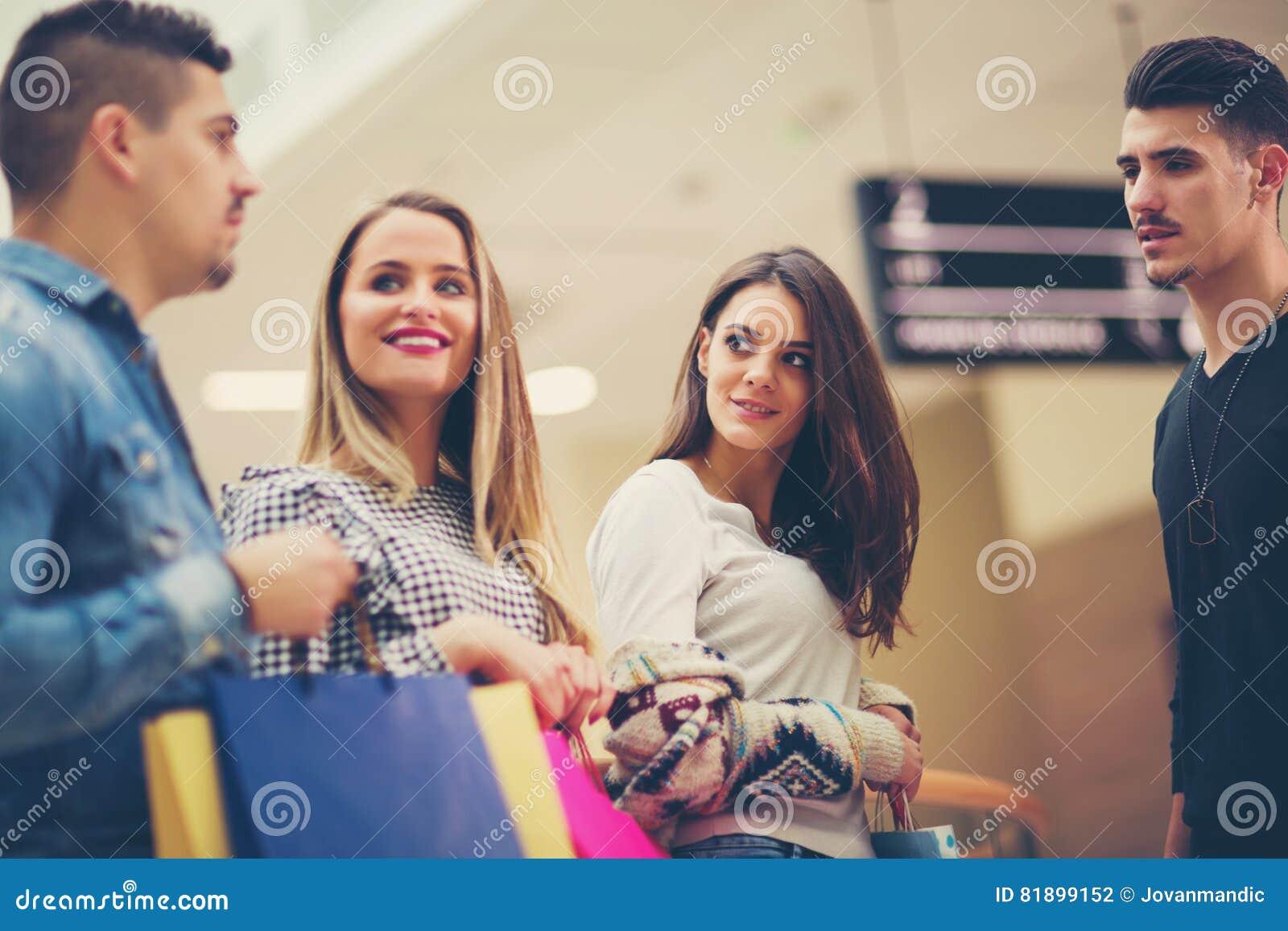 Grupp av vänner som tillsammans shoppar i galleria