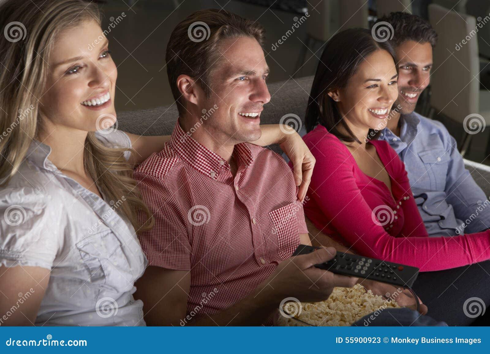 Grupp av vänner som tillsammans sitter på Sofa Watching TV