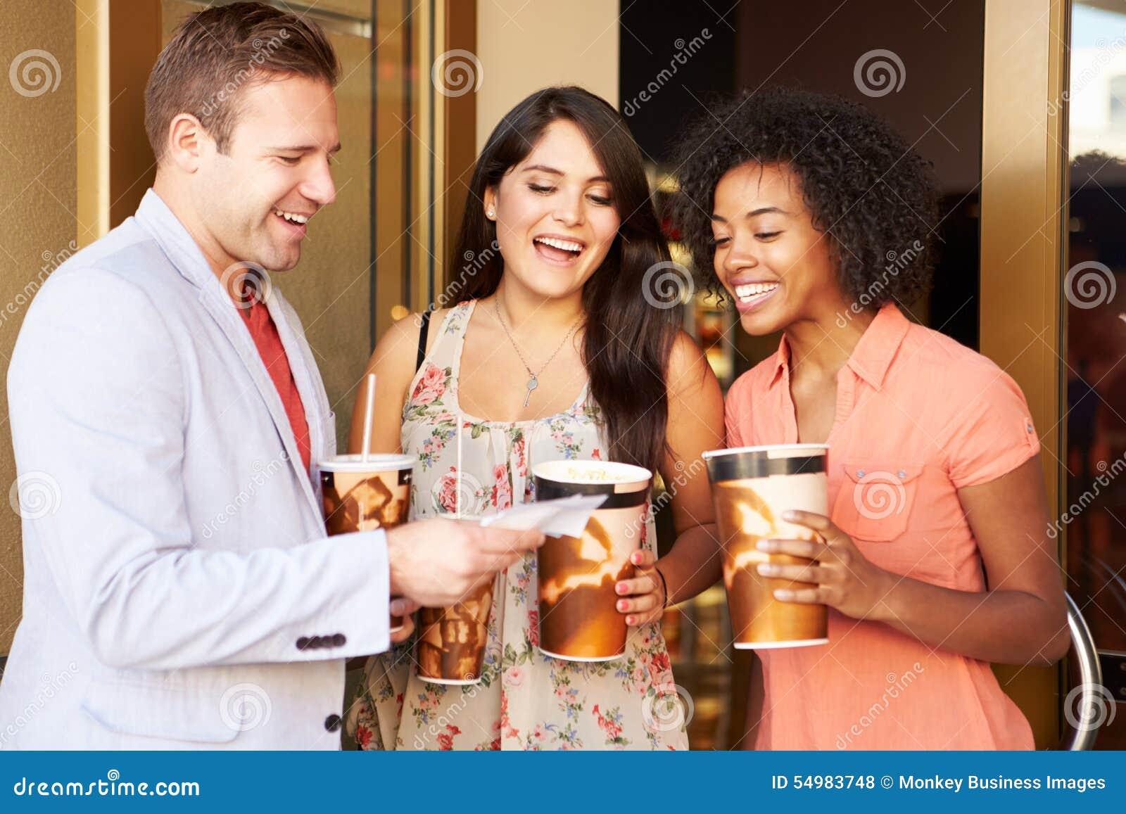 Grupp av vänner som tillsammans står utanför bio