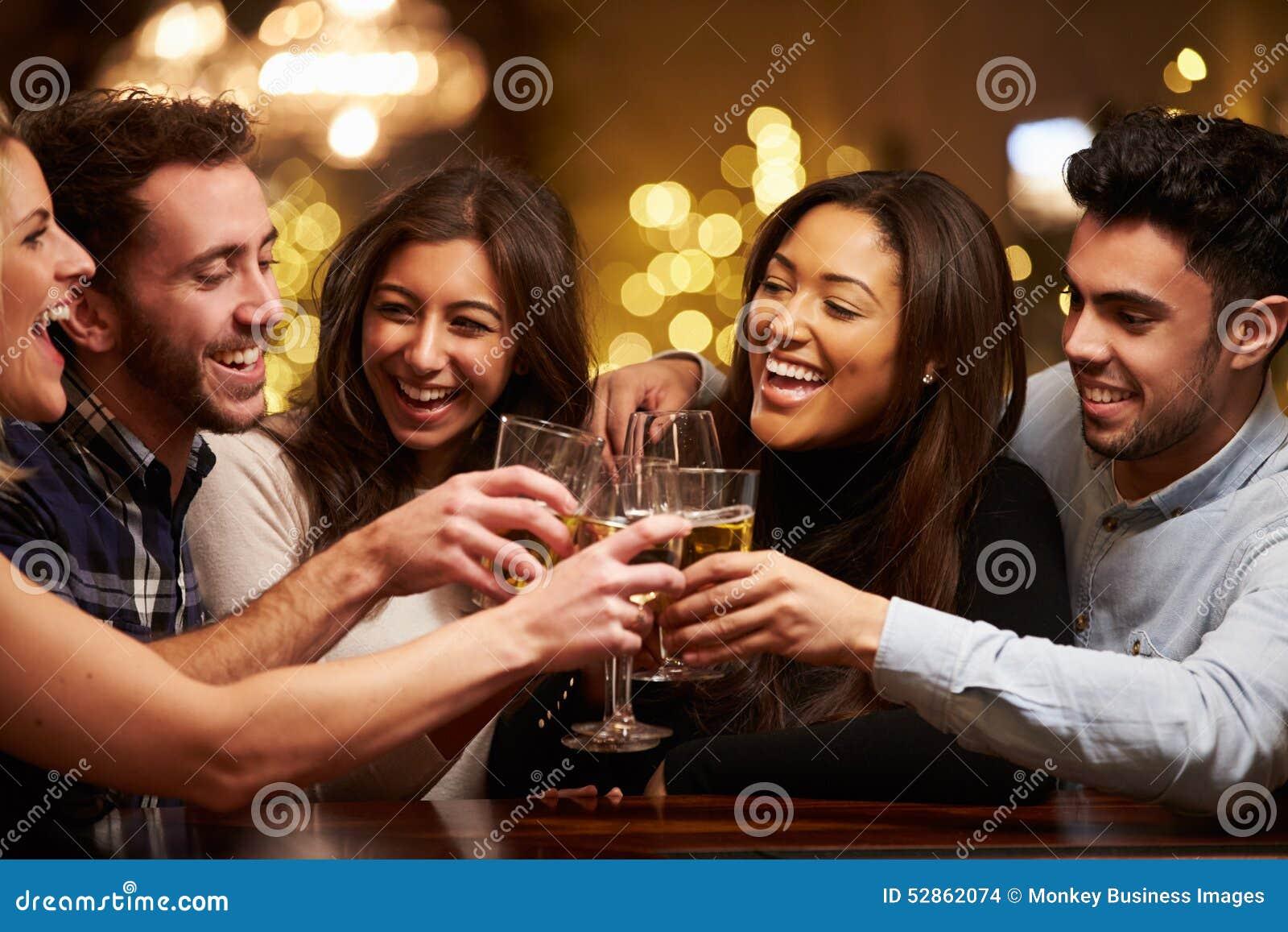 Grupp av vänner som tycker om aftondrinkar i stång
