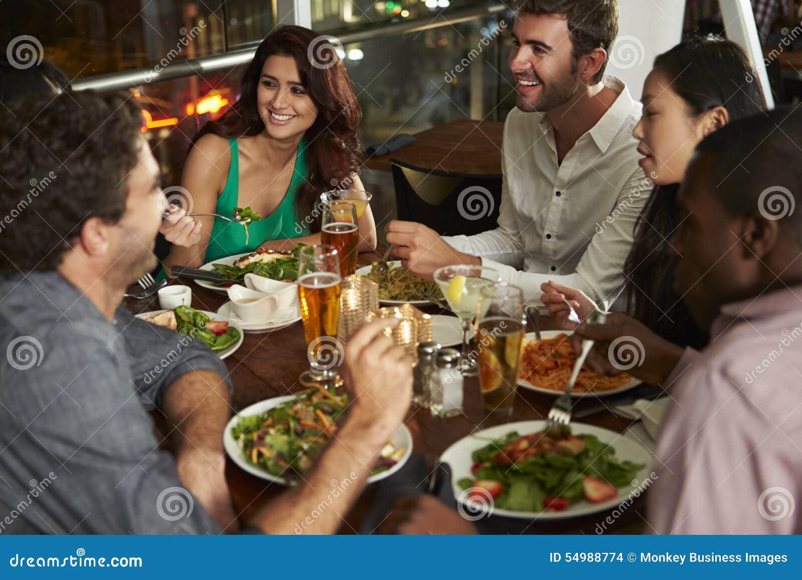 Grupp av vänner som tycker om aftonmål i restaurang