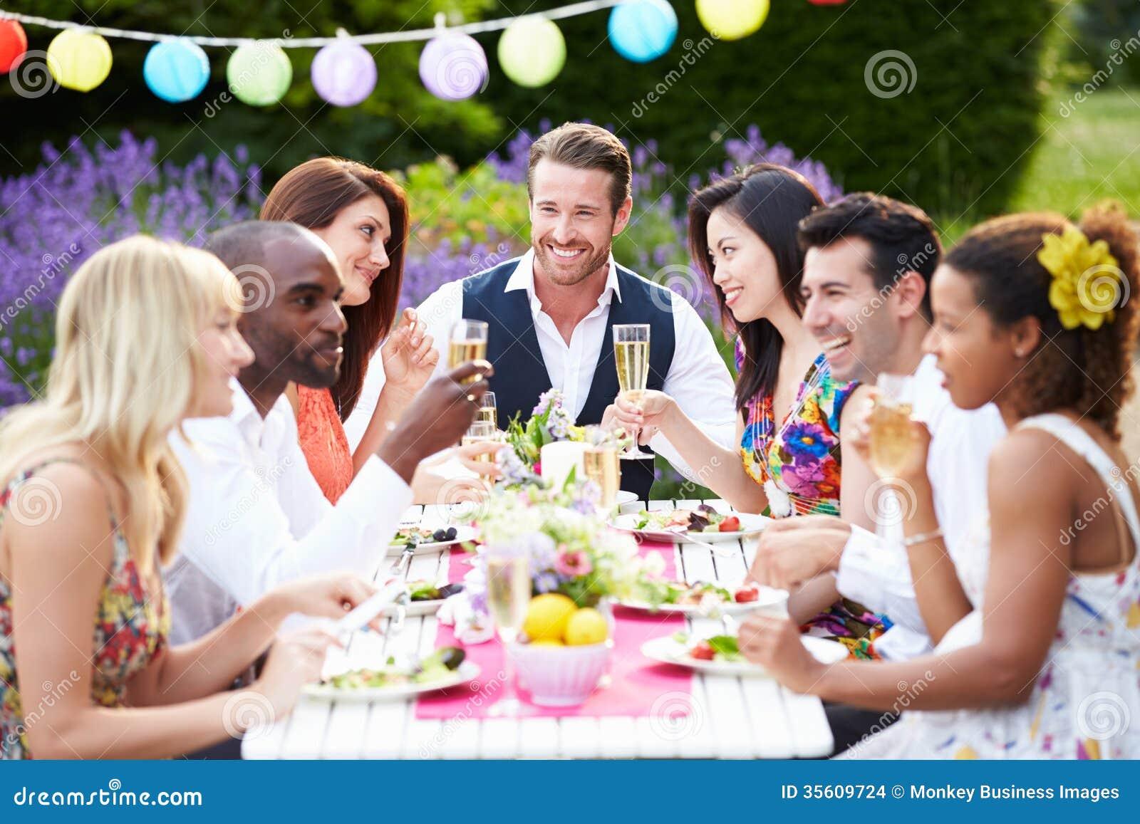 Grupp av vänner som tycker om det utomhus- matställepartiet