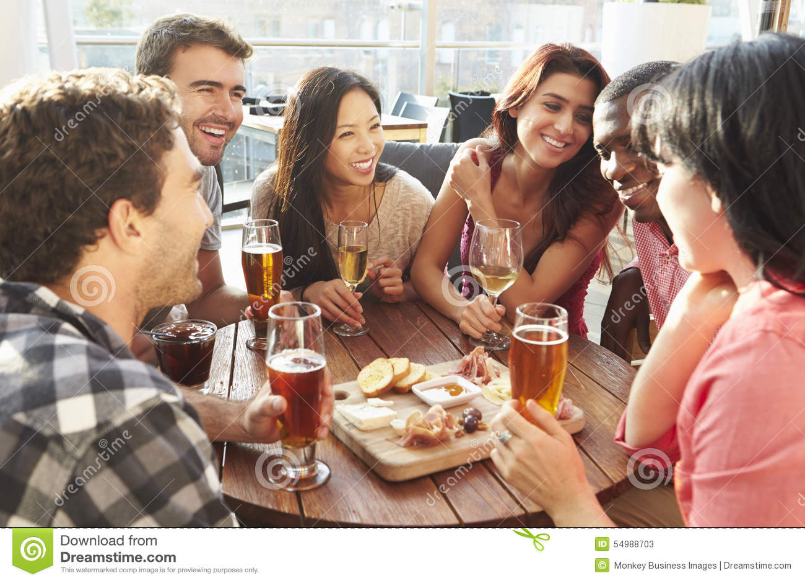 Grupp av vänner som tycker om drinken och mellanmålet i takstång