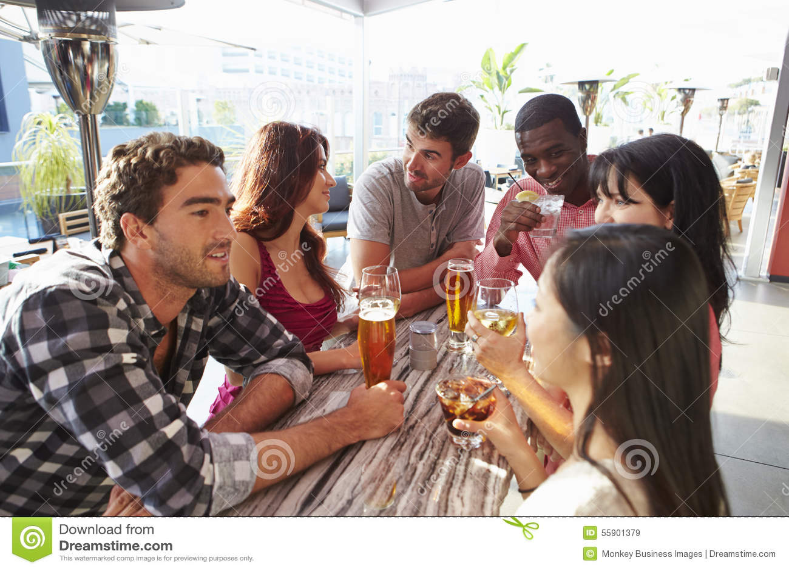 Grupp av vänner som tycker om drinken på den utomhus- takstången