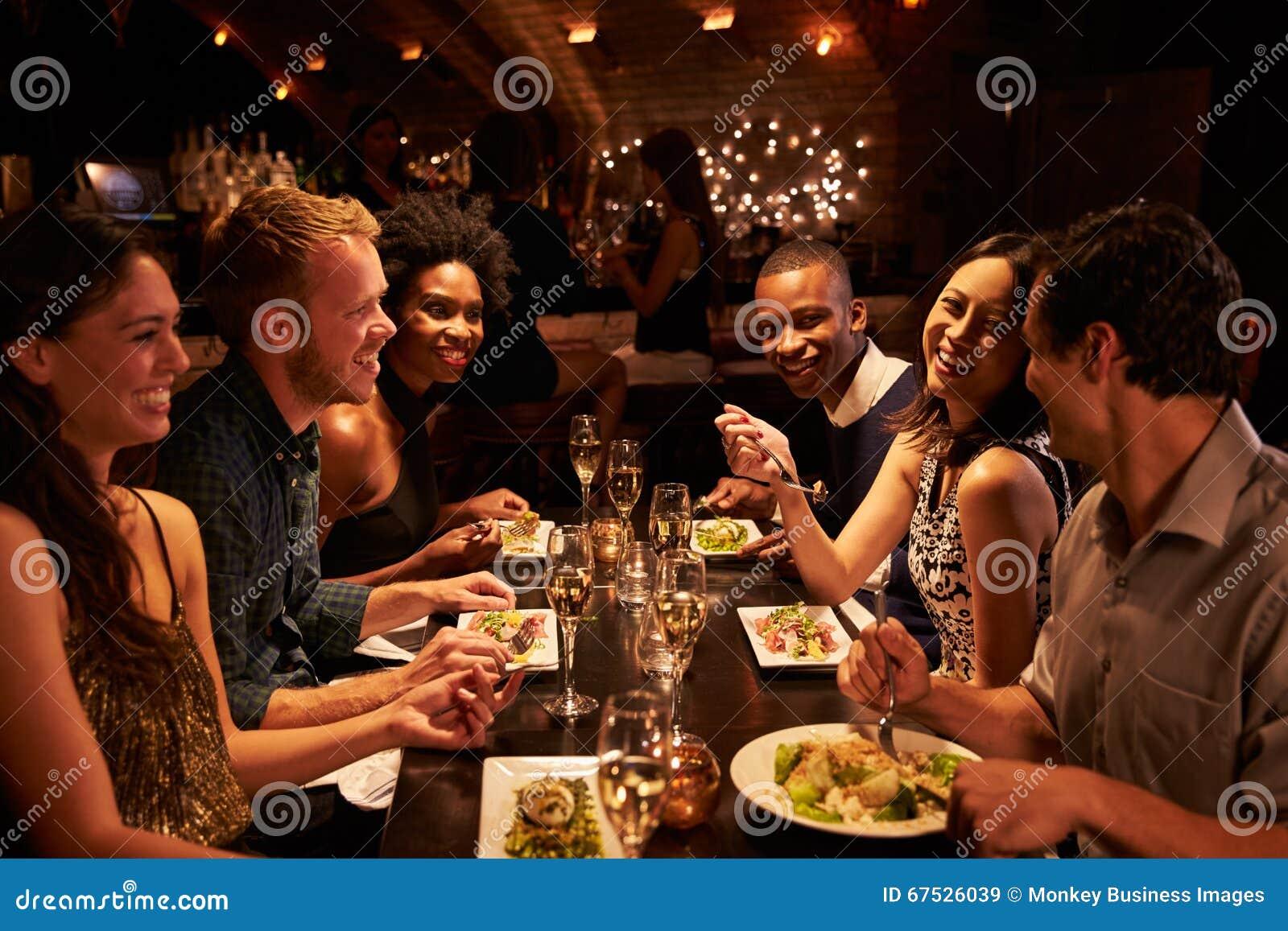 Grupp av vänner som tycker om mål i restaurang