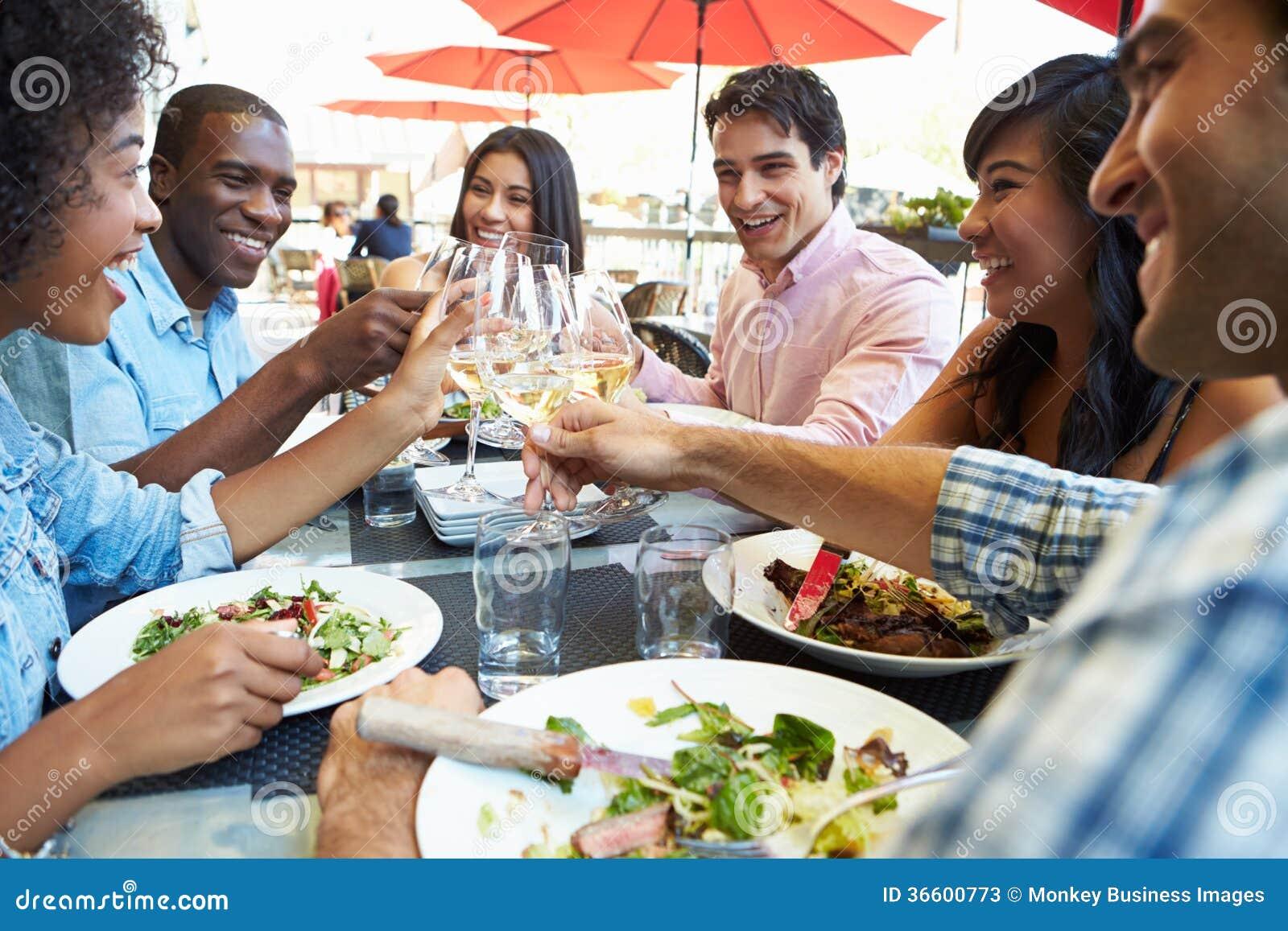 Grupp av vänner som tycker om mål på den utomhus- restaurangen