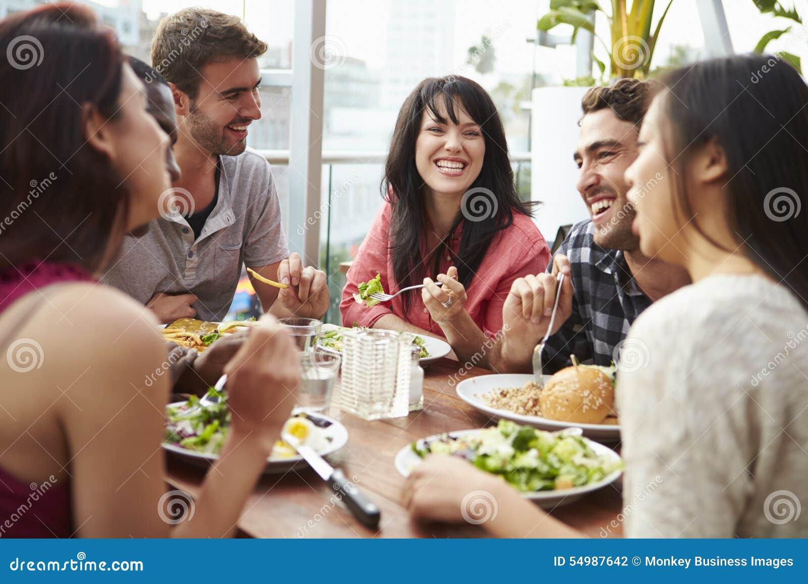 Grupp av vänner som tycker om mål på takrestaurangen