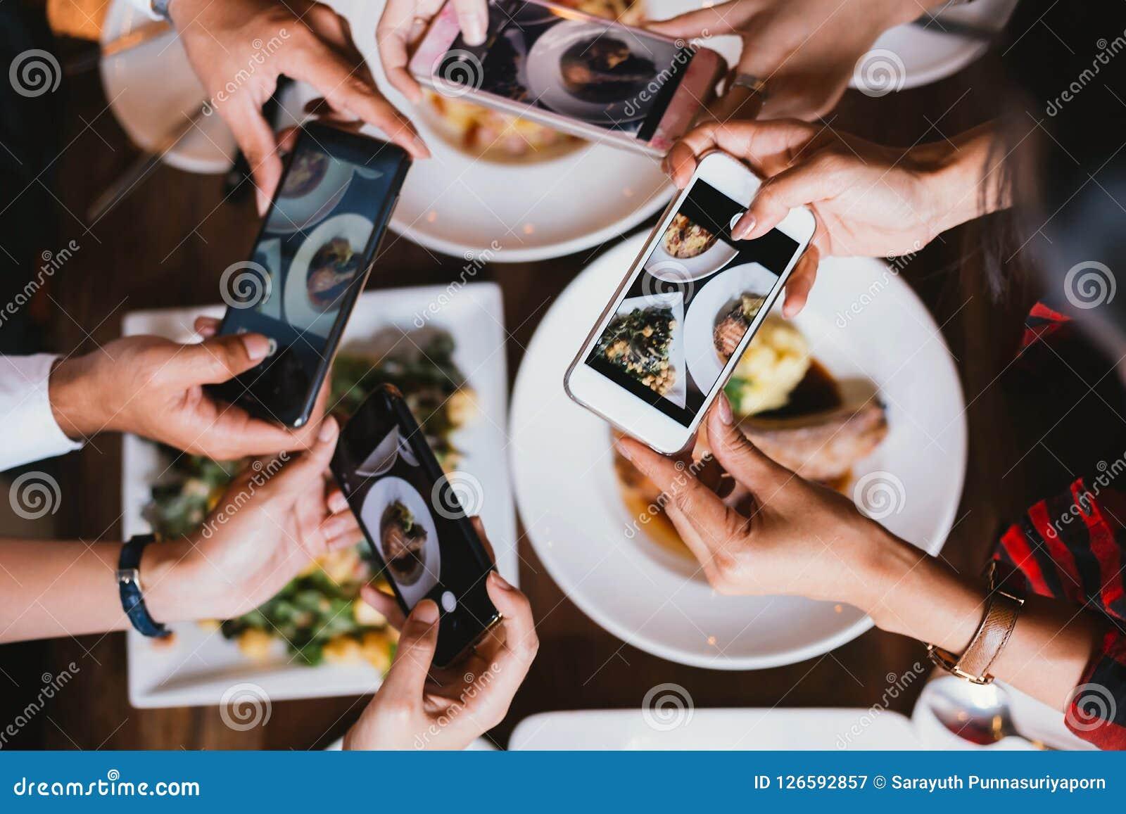 Grupp av vänner som ut går och tar ett foto av italiensk mat samman med mobiltelefonen