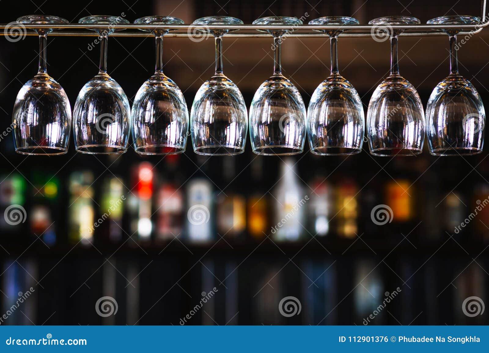 Grupp av vinexponeringsglas som hänger ovanför en stångkugge i bar & restaura