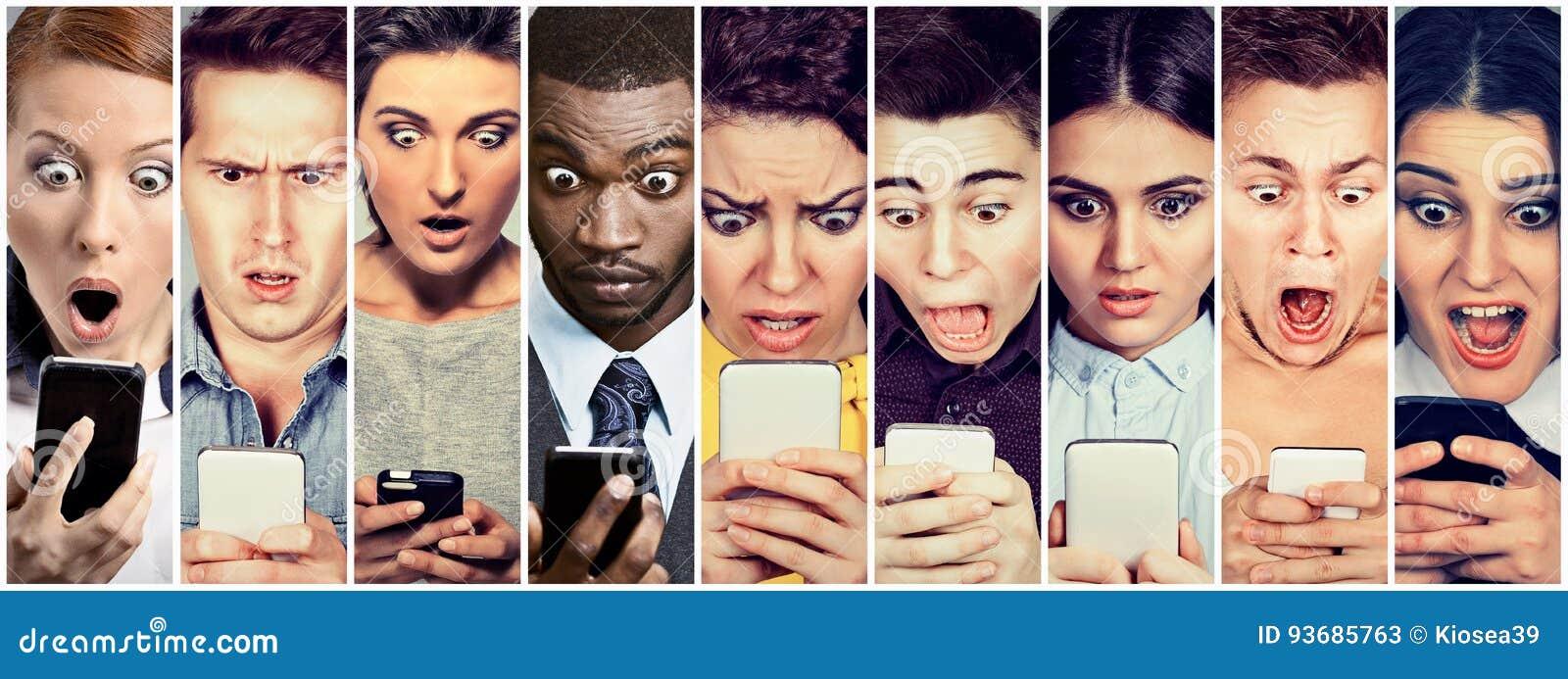 Grupp människormän och kvinnor som ser chockade på mobiltelefonen