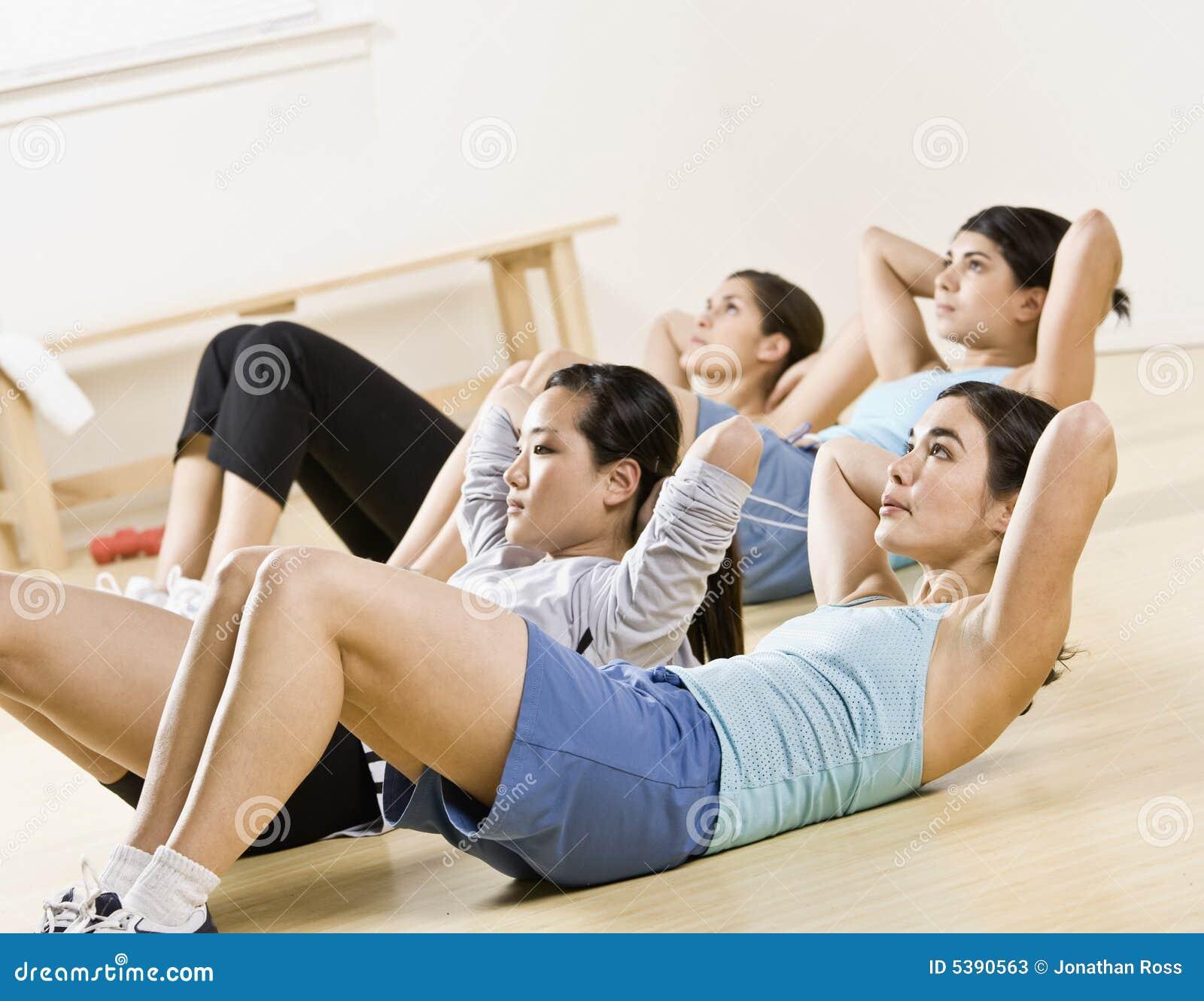 Grupp som gör övning, sitter ups unga kvinnor