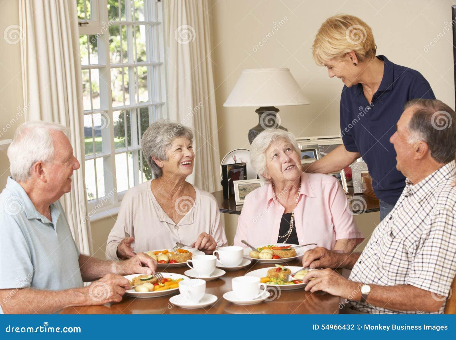 Gruppe ältere Paare Mahlzeit im Pflegeheim mit Haushaltshilfe zusammen genießend