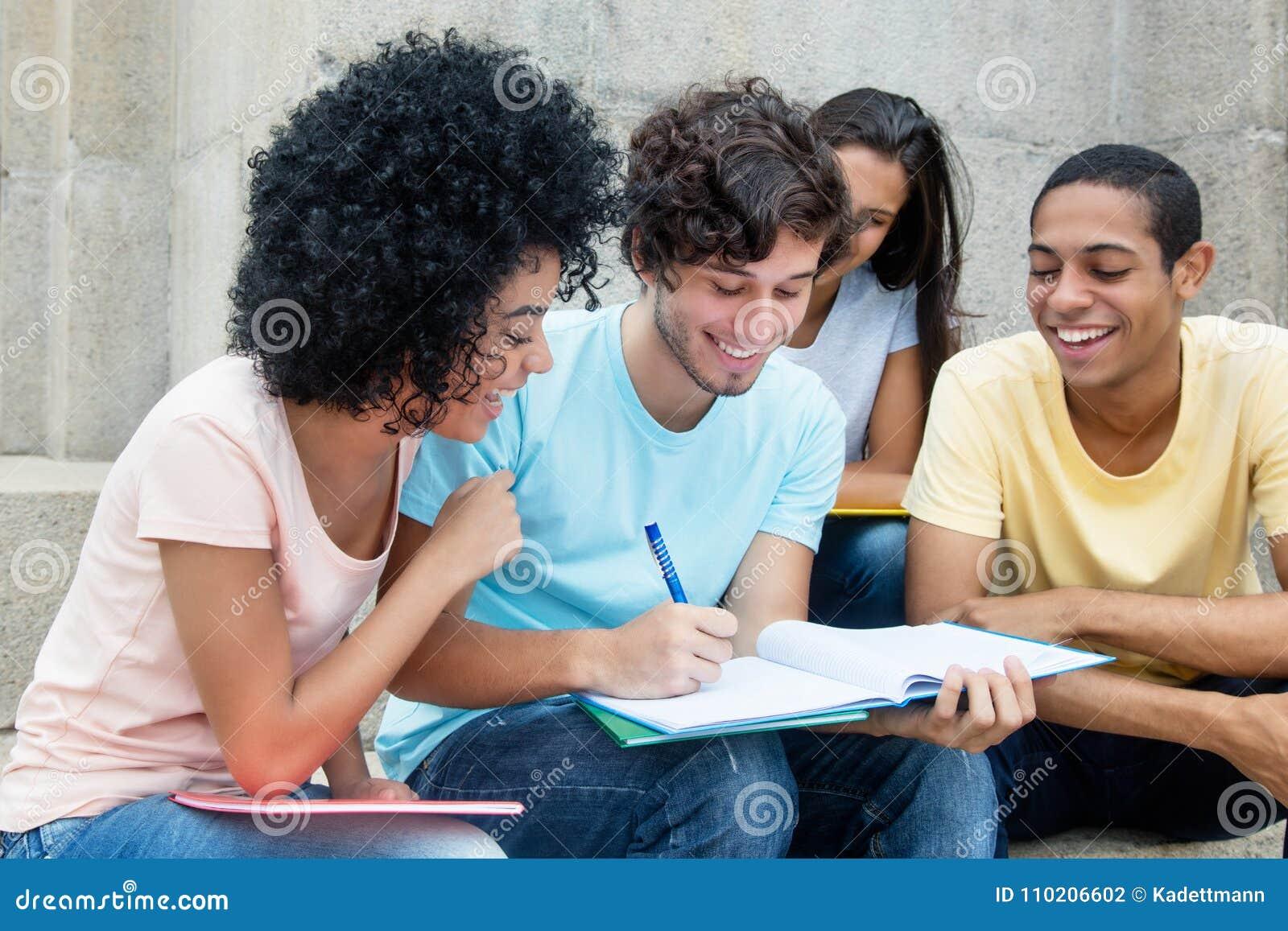 Gruppe amerikanische Studenten, die draußen auf dem Campus lernen