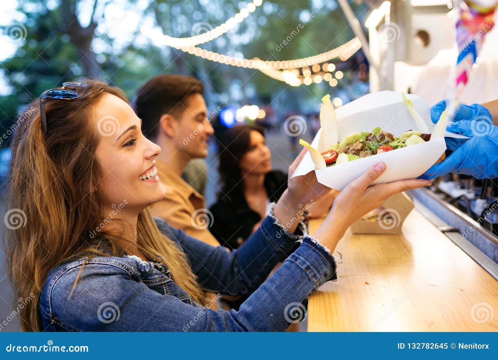 Gruppe attraktive junge Freunde, die verschiedene Arten des Schnellimbisses essen wählen und kaufen herein, Markt in der Straße