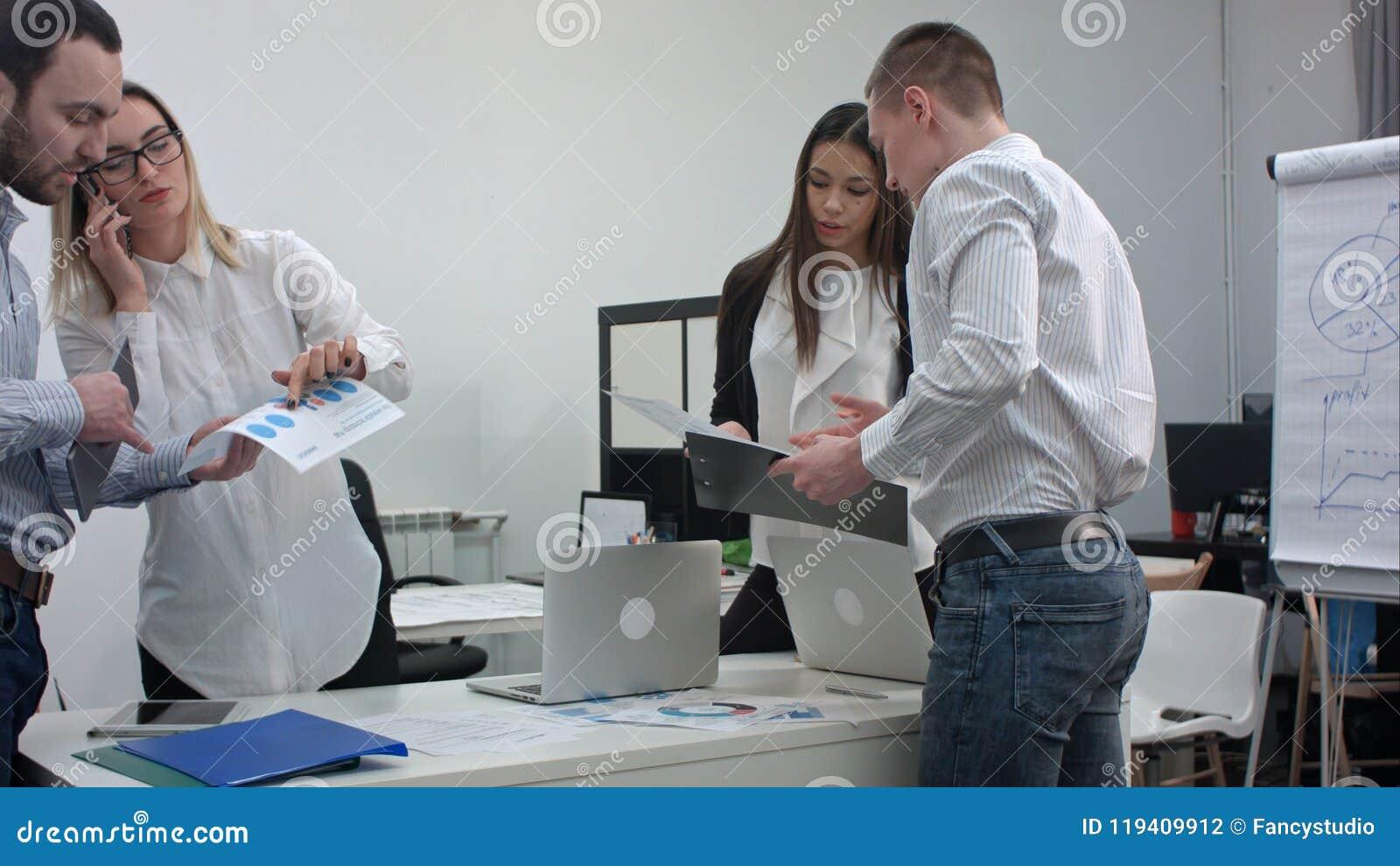 Gruppe Büroangestellte mit den Diagrammen, die für Geschäftsdarstellung sich vorbereiten