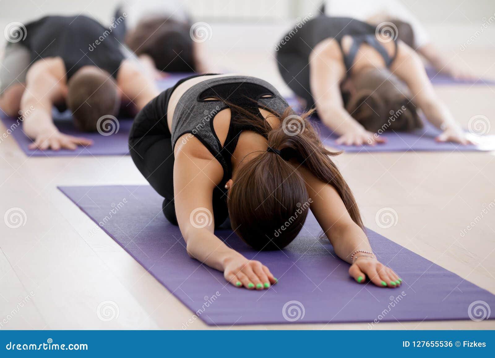 Gruppe der übenden Yogalektion der jungen sportlichen Leute, Kind-exerc