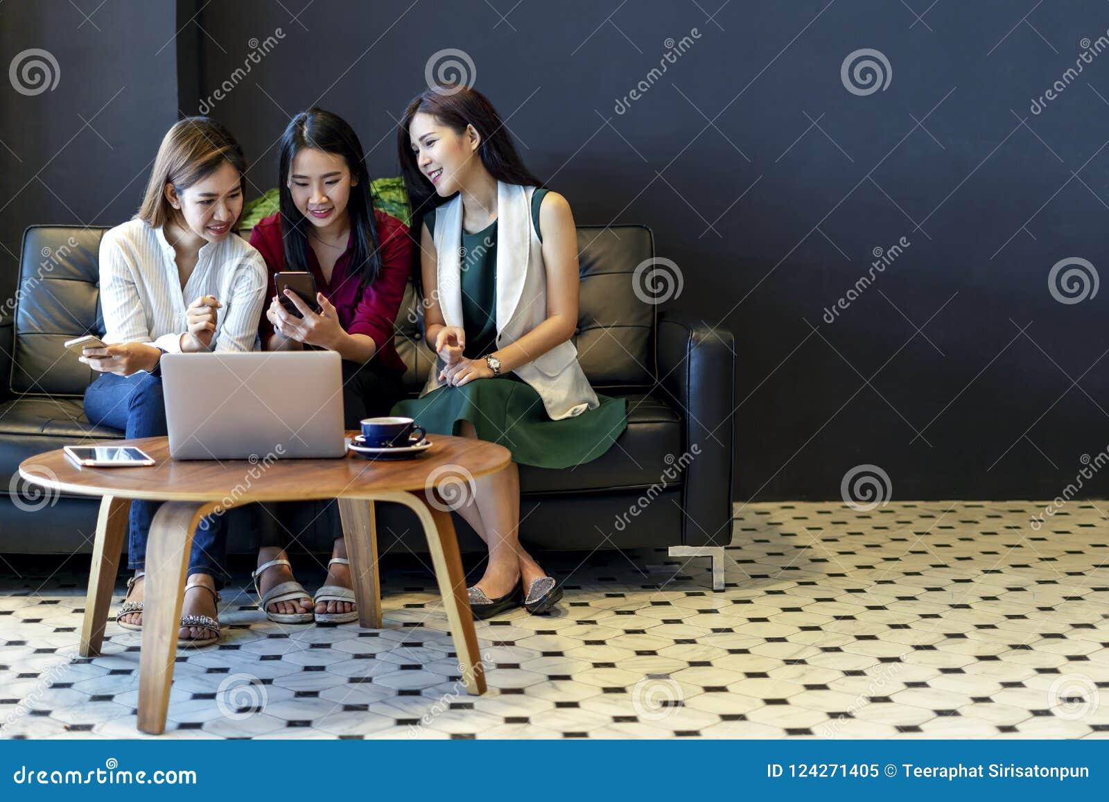 Gruppe des Bezauberns von den schönen Asiatinnen, die Smartphone und Laptop, plaudernd auf Sofa am Café, moderner Lebensstil verw