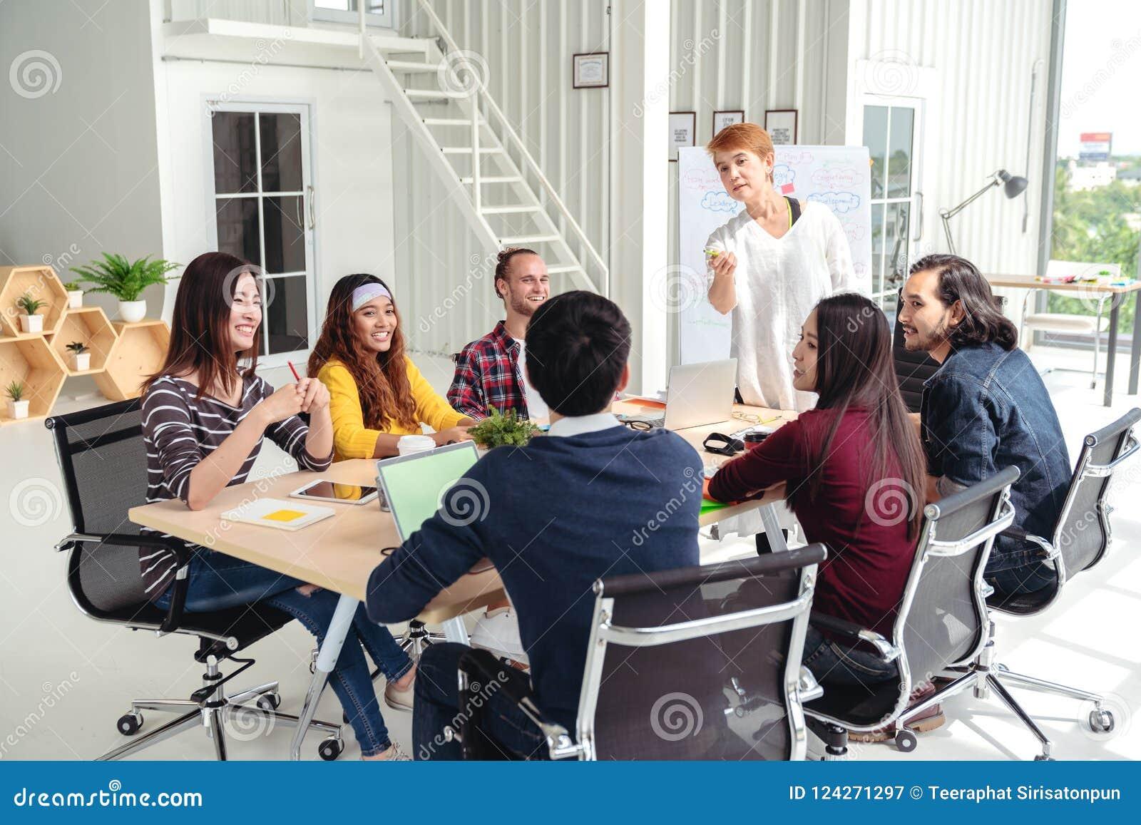 Gruppe des gemischtrassigen jungen kreativen Teams, das in der Sitzung am modernen Bürokonzept spricht, lacht und gedanklich löst