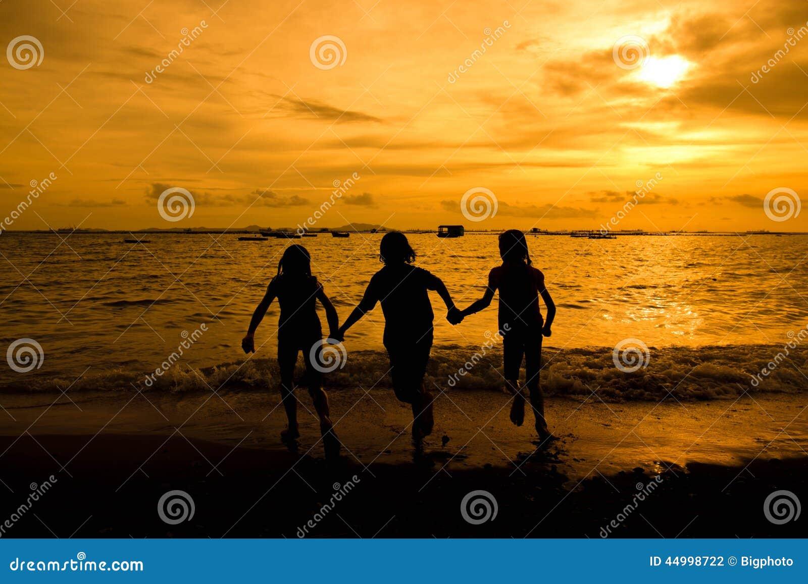 Gruppe des glücklichen jungen Mädchens, das am Strand auf schöner Summe läuft