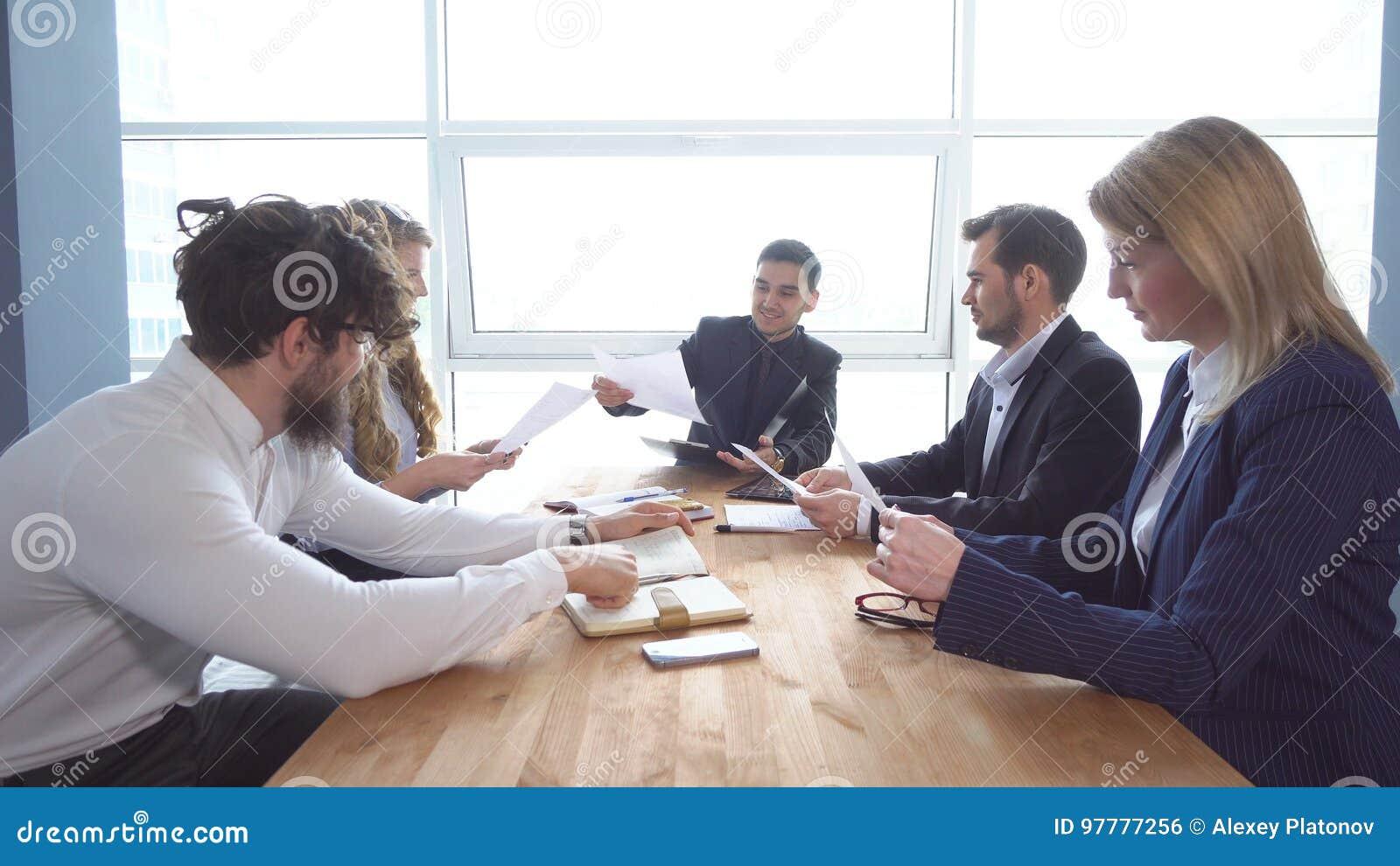 Gruppe des jungen Geschäftsmannes am Verhandlungstisch im Büro Kollegeblick durch Dokumente Ein Geschäftstreffen