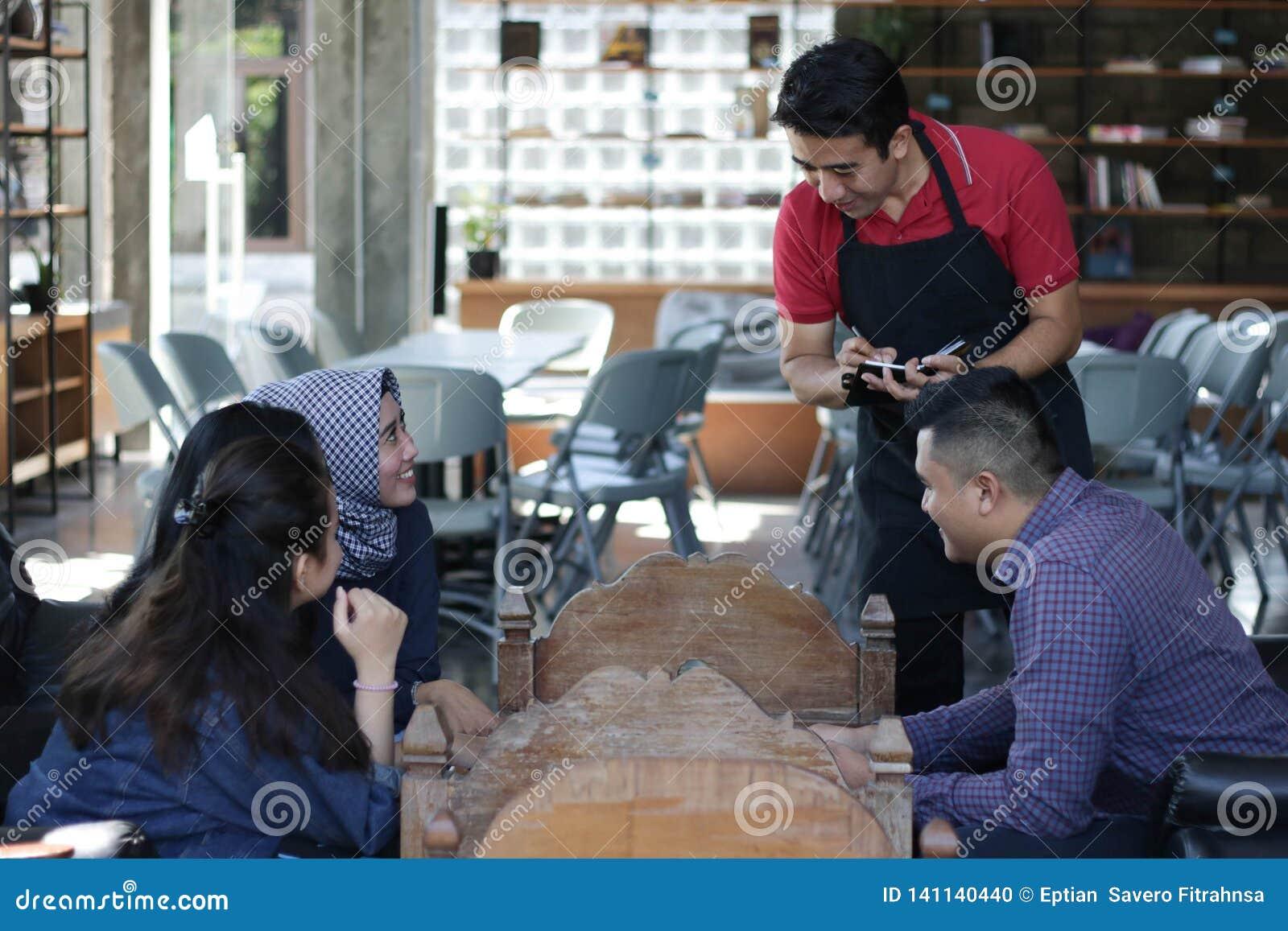 Gruppe des jungen glücklichen Freunds, der vom Menü bestellt, während Kellner die Aufträge am Café und am Restaurant schreiben