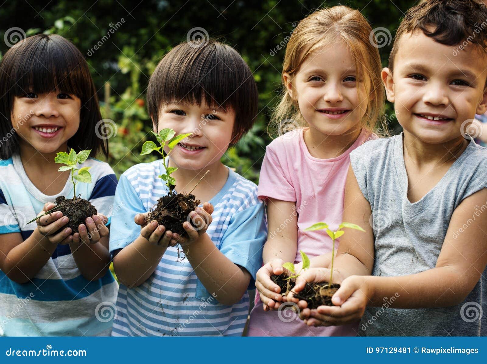 Gruppe des Kindergartens scherzt die Gartenarbeitlandwirtschaft der Freunde