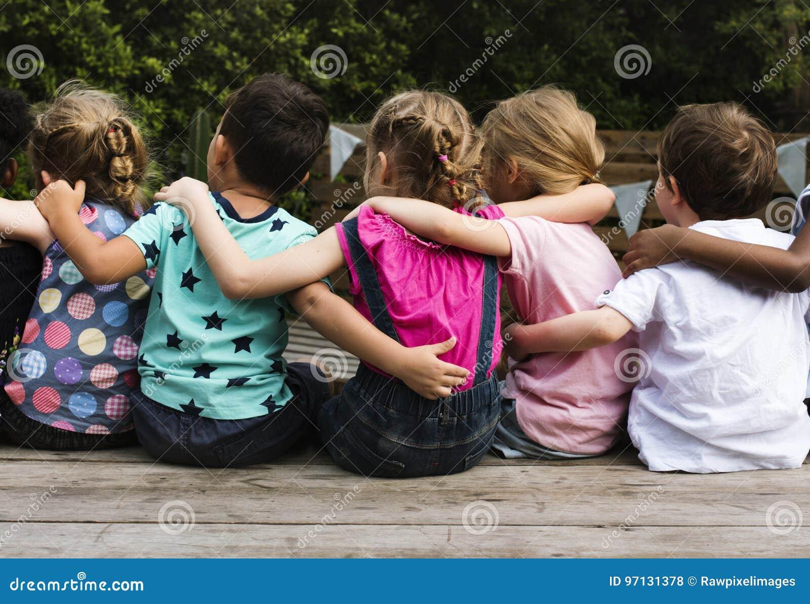 Gruppe des Kindergartens scherzt Freunde bewaffnen um zusammen sitzen