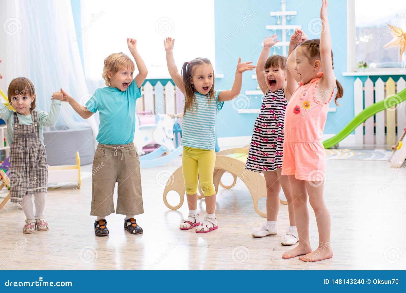 Gruppe emotionale Freunde mit ihren Händen hob an Kinder haben Spaßzeitvertreib im Kindertagesstätte