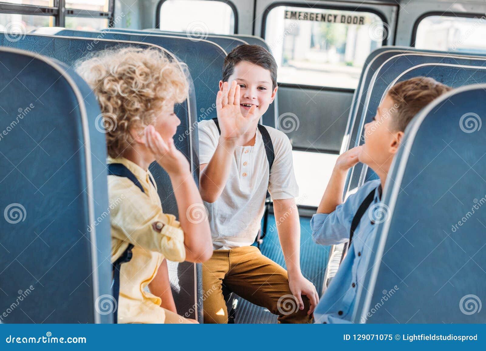 Gruppe entzückende Schüler, die zusammen hohe fünf beim Reiten geben