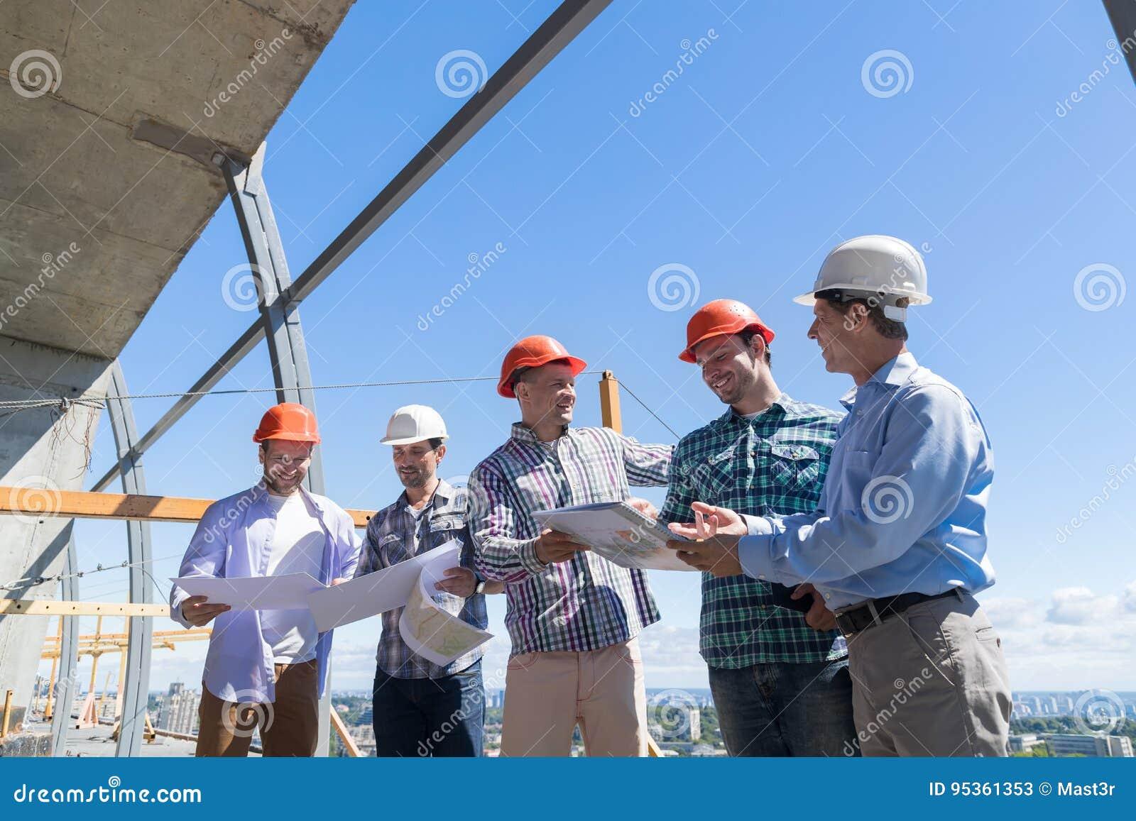 Gruppe Erbauer im Hardhat Projekt-Plan mit Architekten On Constuction Site besprechend, das zusammenarbeitet