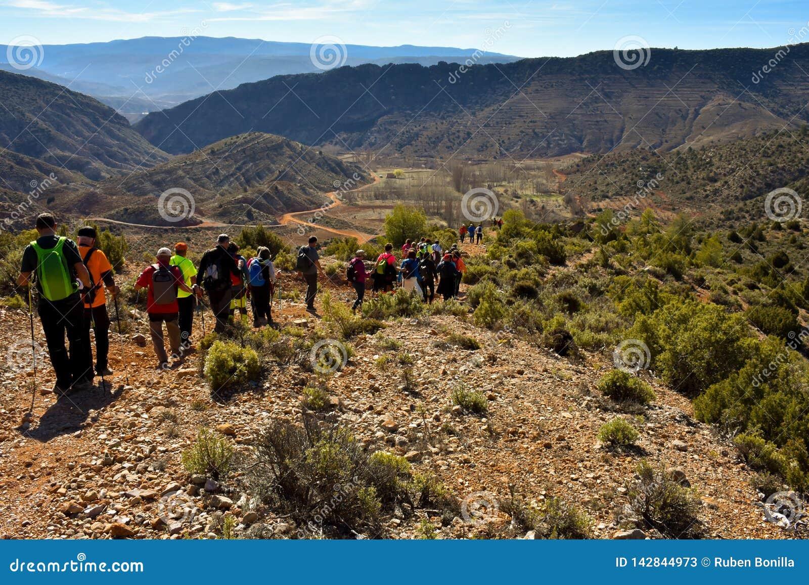 Gruppe erwachsene Leute mit buntem Rucksacktrekking auf einem Weg des Sandes und der Steine gehend hinunter einen Berg mit einem