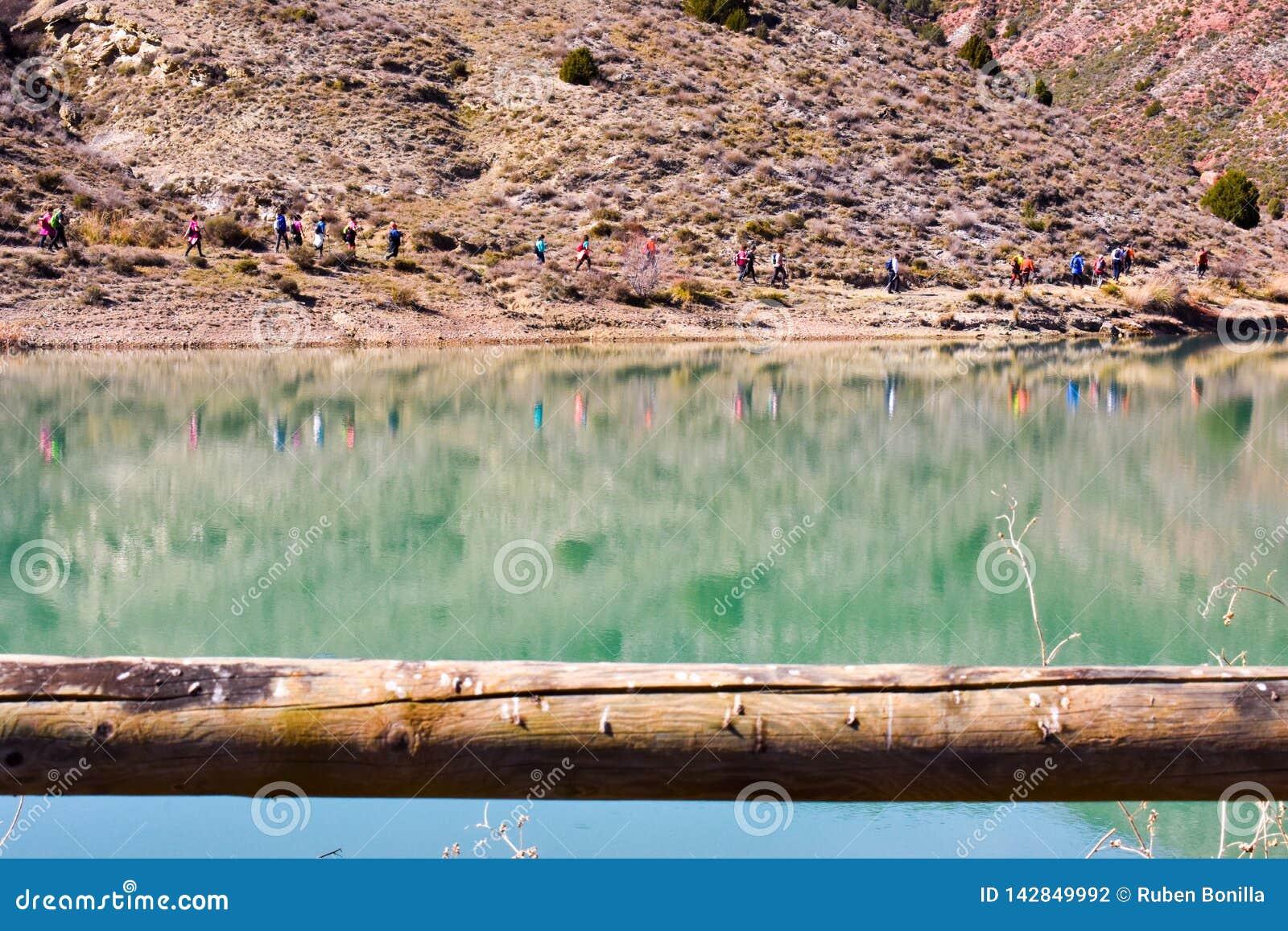 Gruppe erwachsene Leute mit buntem Rucksacktrekking auf einem Weg des Sandes und der Steine gehend nahe bei einem See, der ihre B