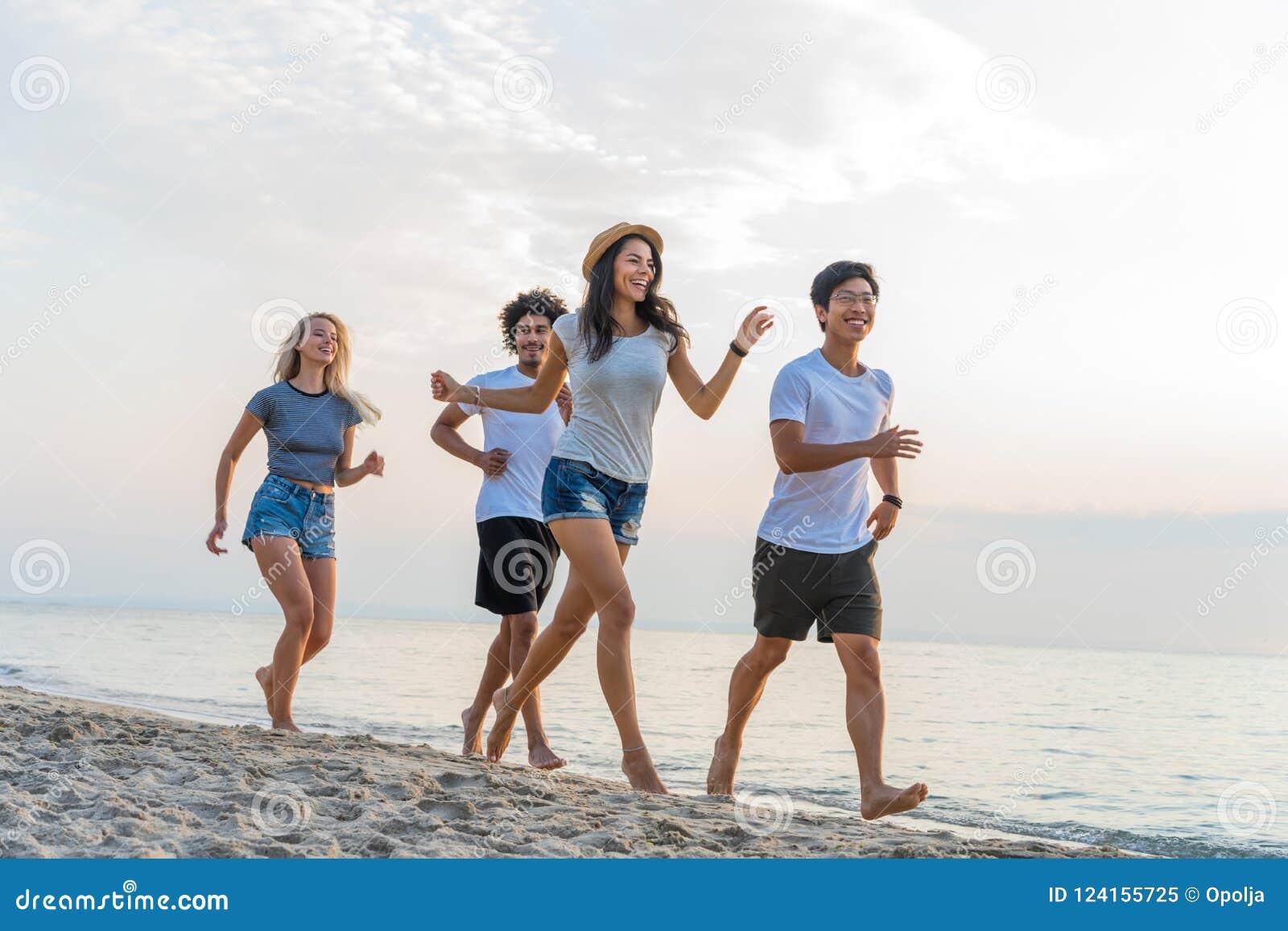 Gruppe Freunde, die den Spaß läuft hinunter den Strand bei Sonnenuntergang haben