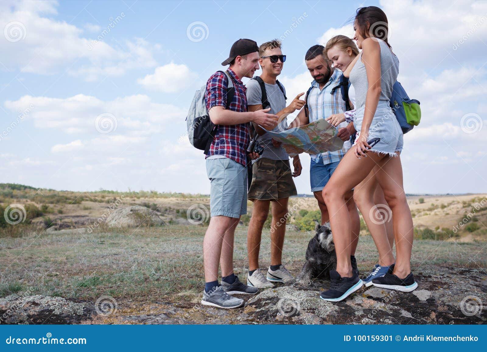 Gruppe Freunde, die Karte betrachten und sich draußen besprechen Freunde gehen am Wandern, Wald, Erholung, lieben aktiven Lebenss
