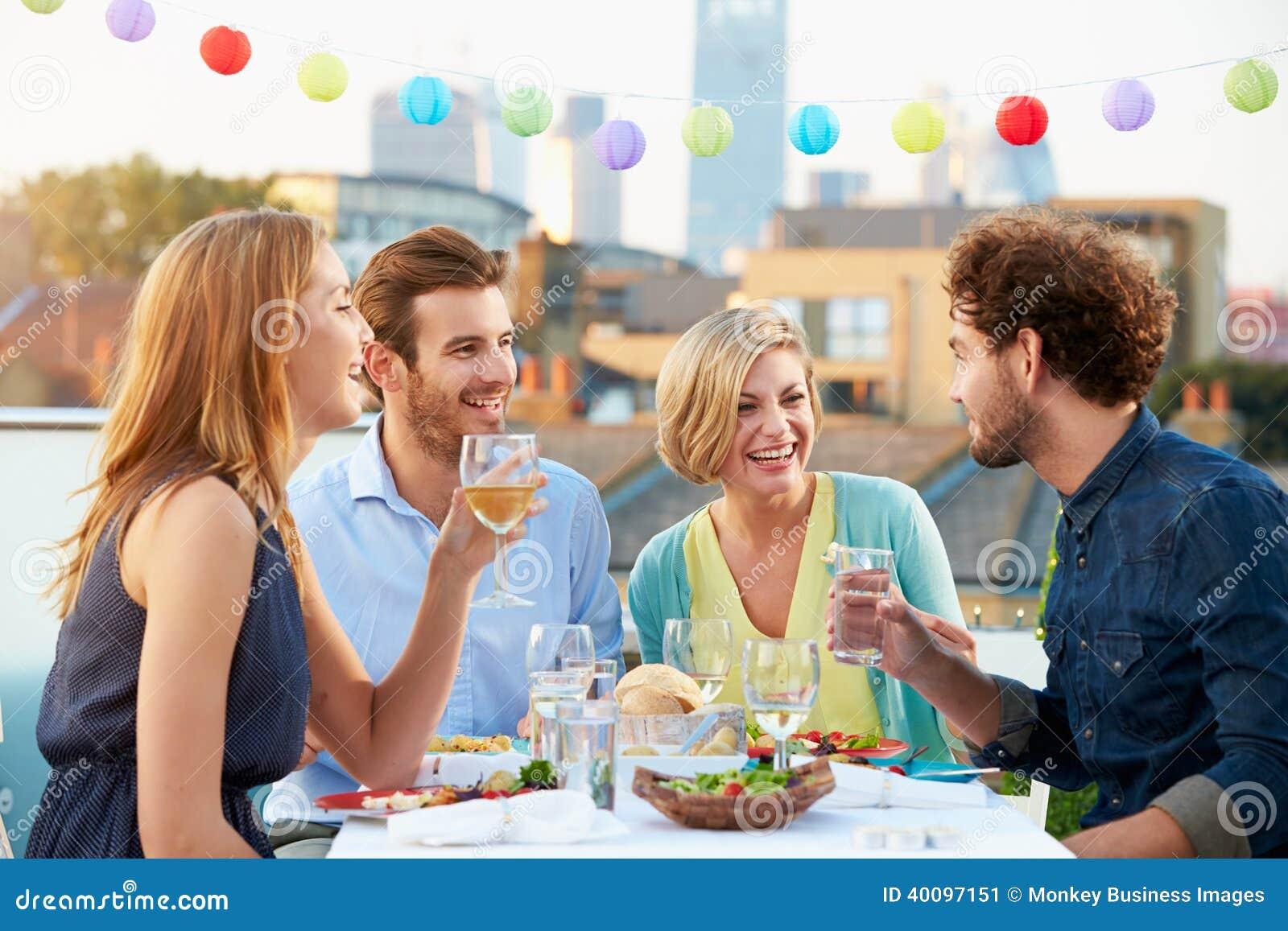 Gruppe Freunde, die Mahlzeit auf Dachspitzen-Terrasse essen