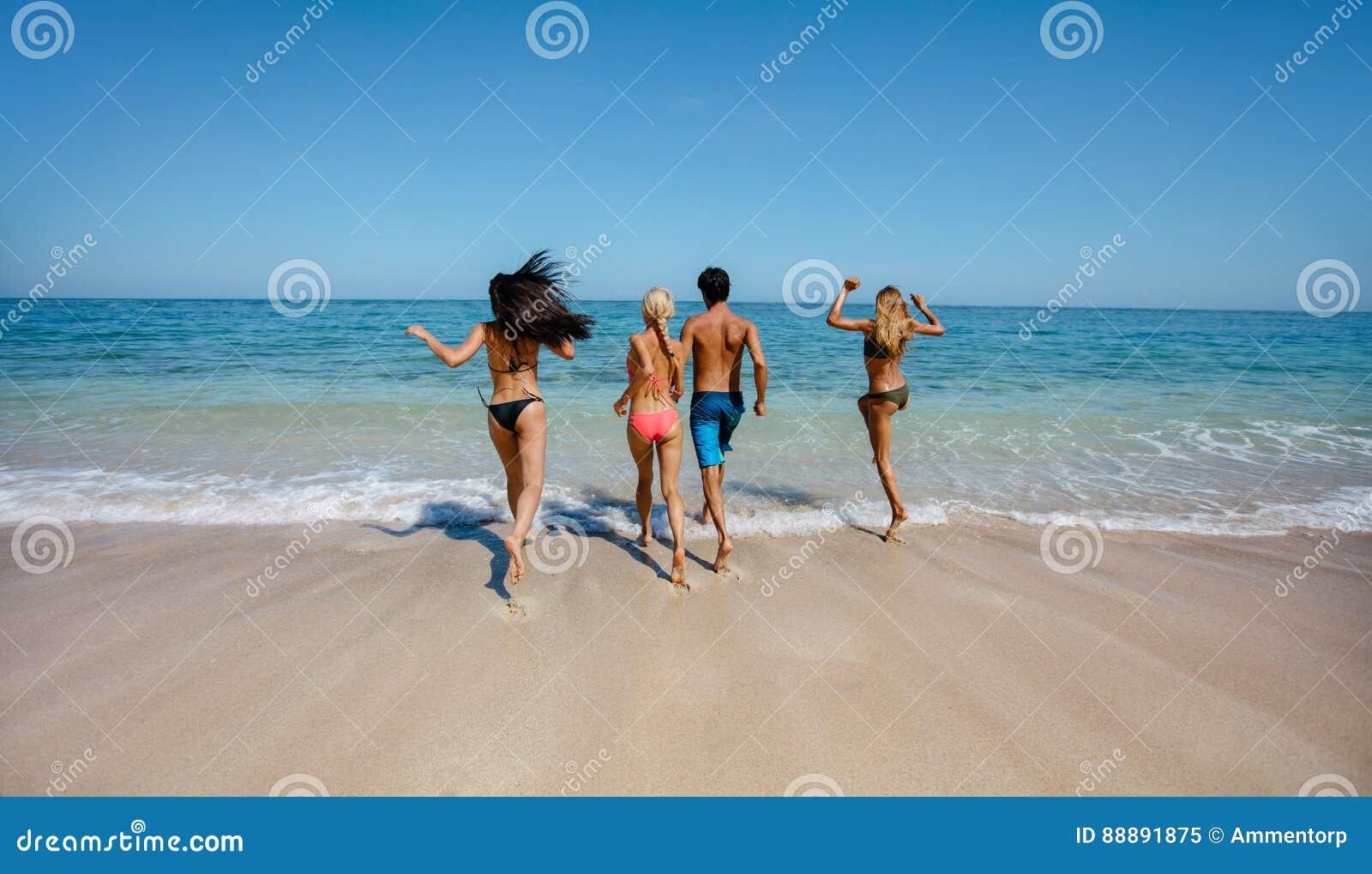 Gruppe Freunde, die in Meerwasser laufen
