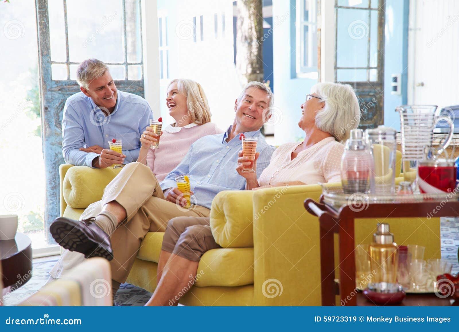 Gruppe Freunde zu Hause, die im Aufenthaltsraum mit kalten Getränken sich entspannen