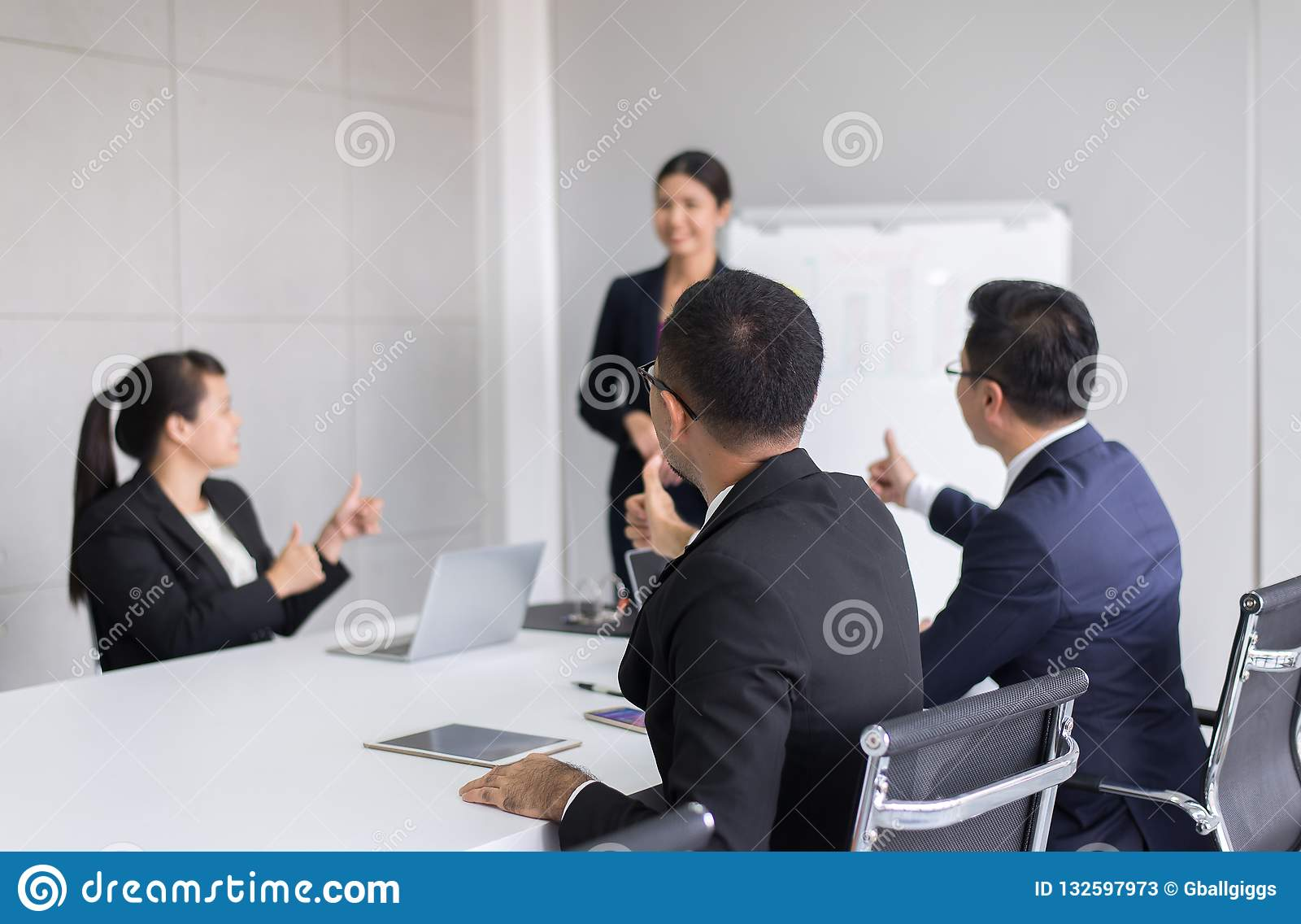 Gruppe Geschäftsleute tumb herauf Hände zum Sprecher nach dem Treffen, Erfolgsdarstellung und Anleitungsseminar im modernen Büro