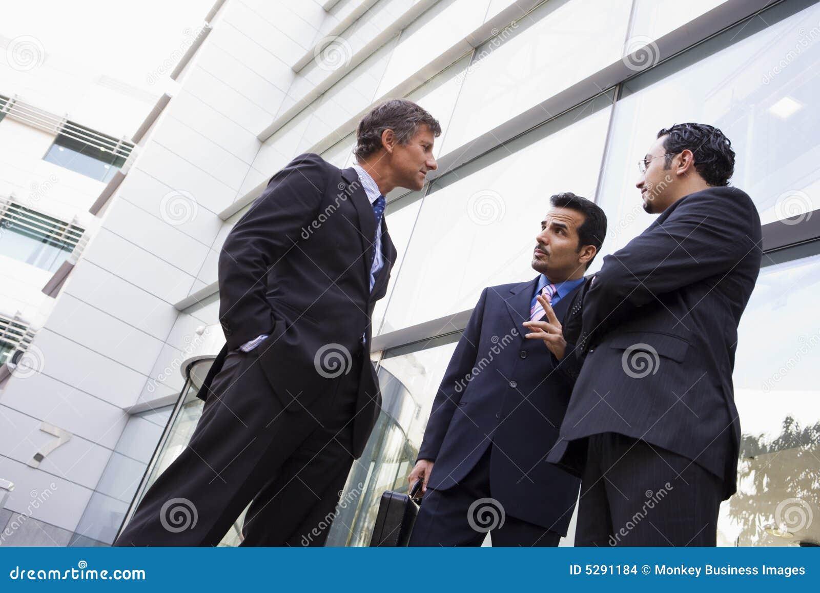 Gruppe Geschäftsmänner, die außerhalb des Büro buildi sprechen