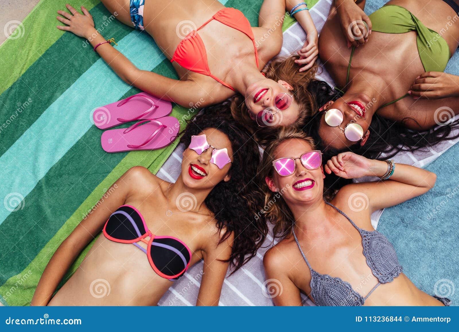 Gruppe glückliche Frauen, die heraus am Poolside hängen