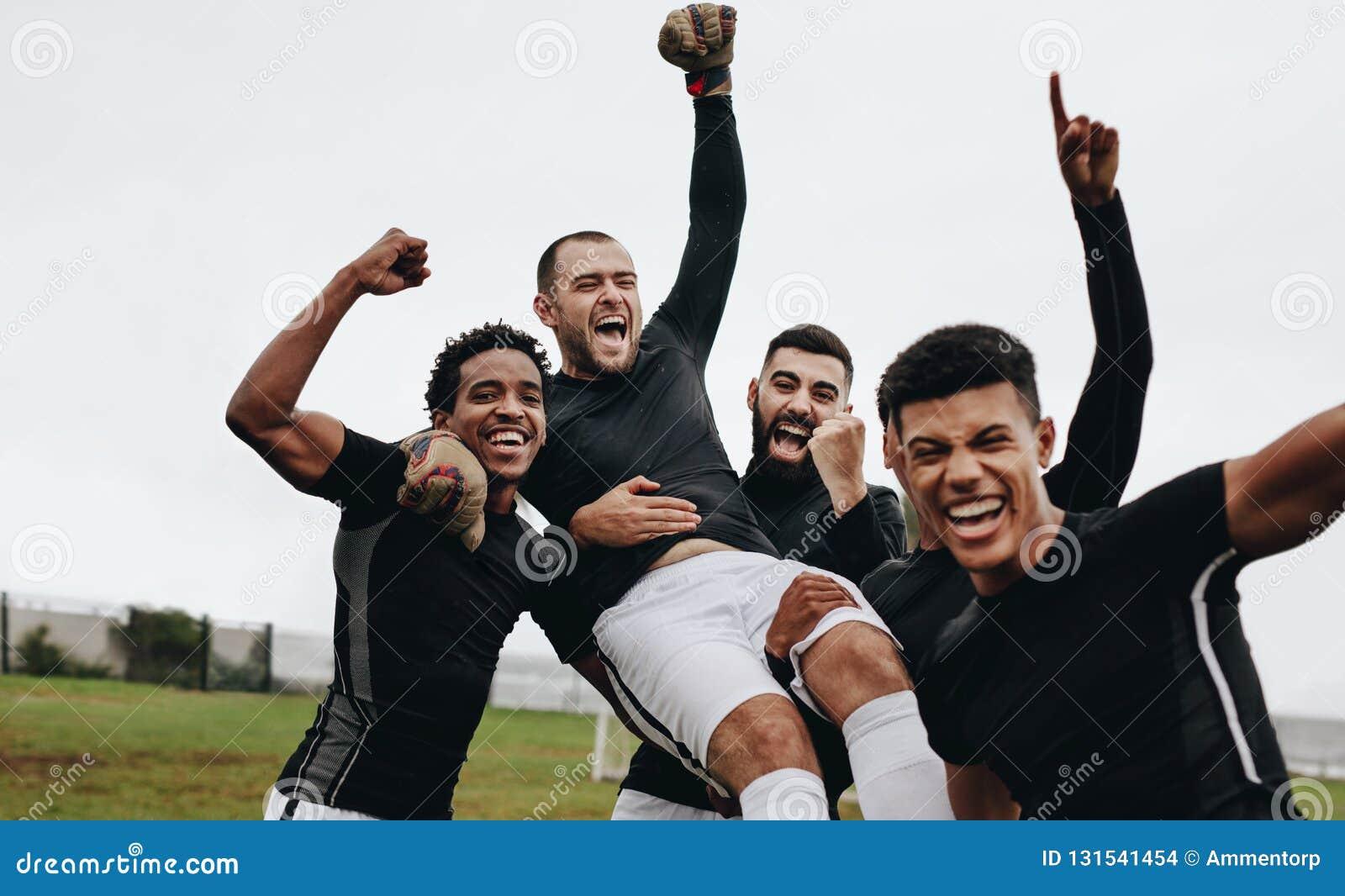 Gruppe glückliche Fußballspieler, die einen Gewinn durch das Anheben ihres Torhüters feiern Fußballspieler, die Sieg durch das An