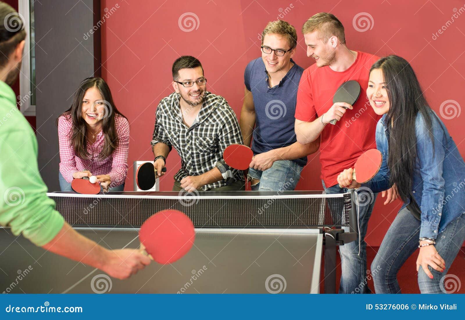 Gruppe glückliche junge Freunde, die Klingeln pong Tischtennis spielen