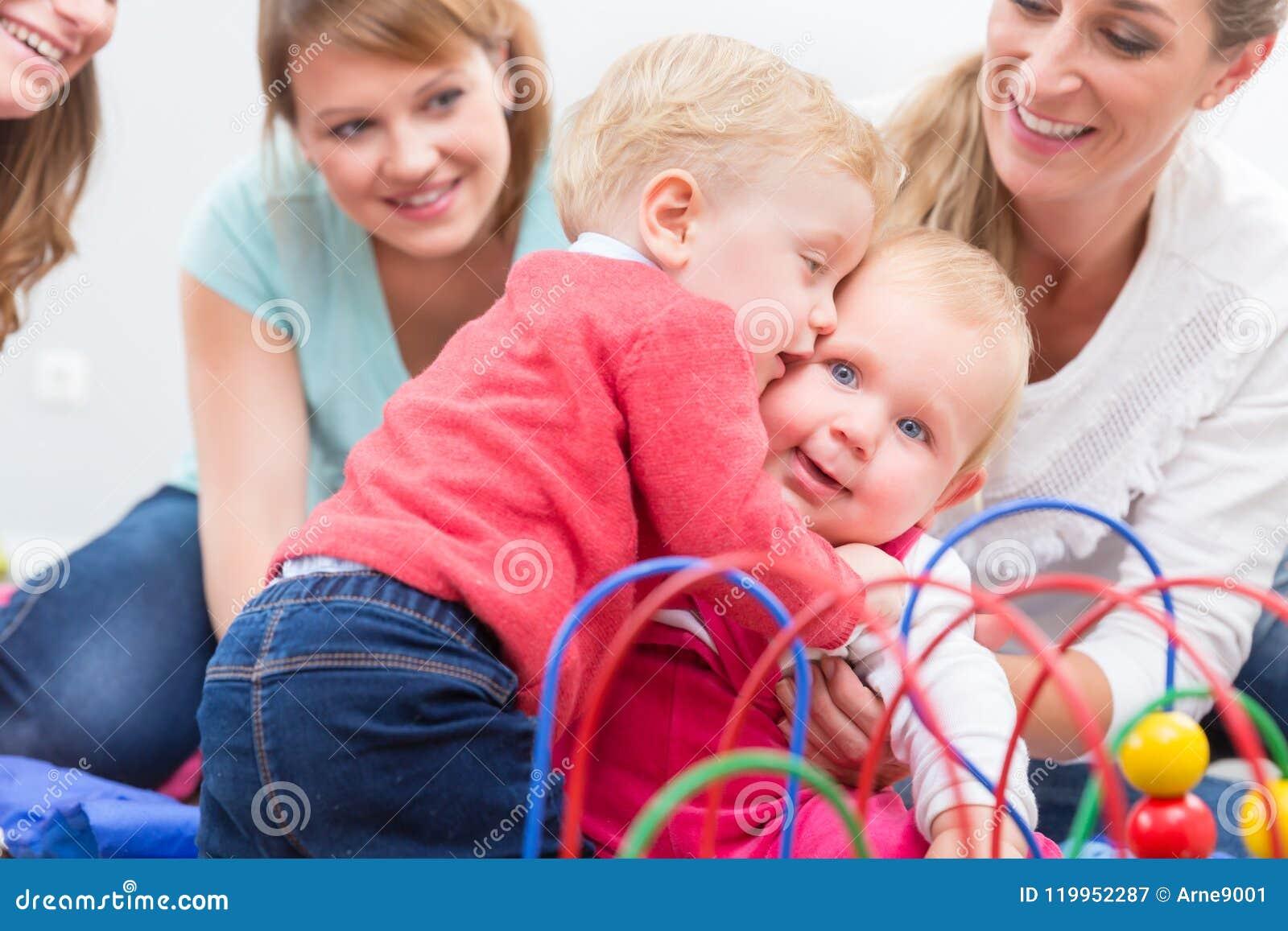 Gruppe glückliche junge Mütter, die ihre netten und gesunden Babys aufpassen, spielen