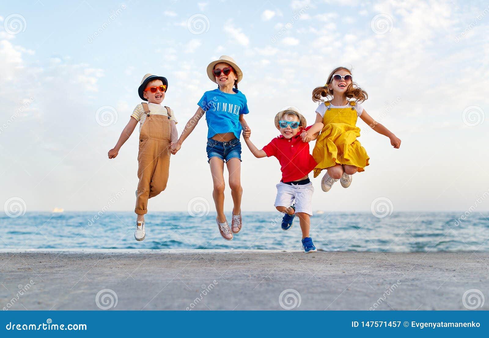 Gruppe glückliche Kinder springen durch Meer im Sommer