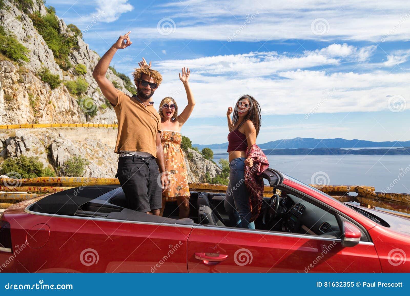 Gruppe glückliche Menschen im roten konvertierbaren Auto