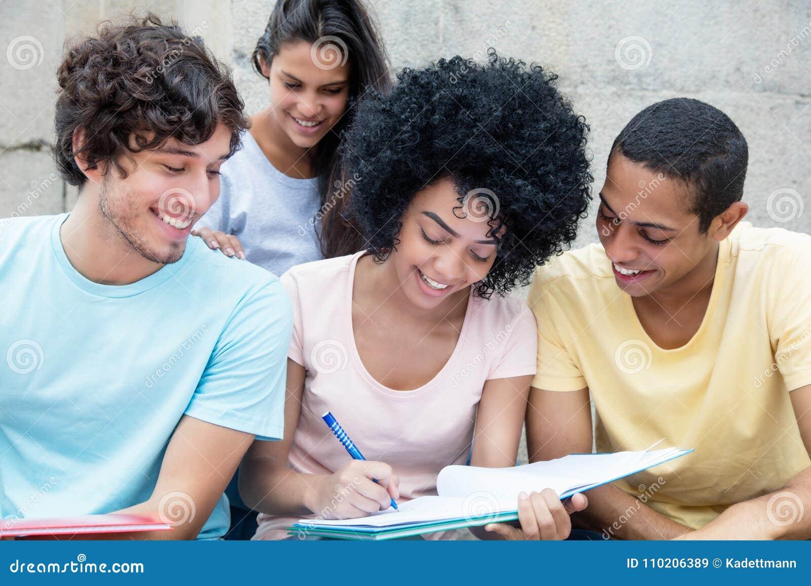 Gruppe glückliche Studenten, die draußen auf dem Campus lernen