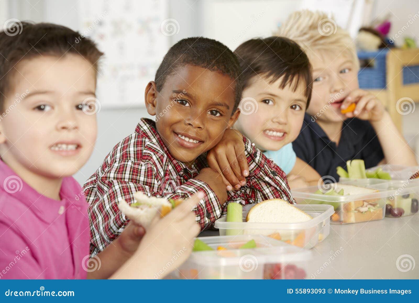 Gruppe grundlegende Alters-Schulkinder, die gesundes verpacktes Lun essen