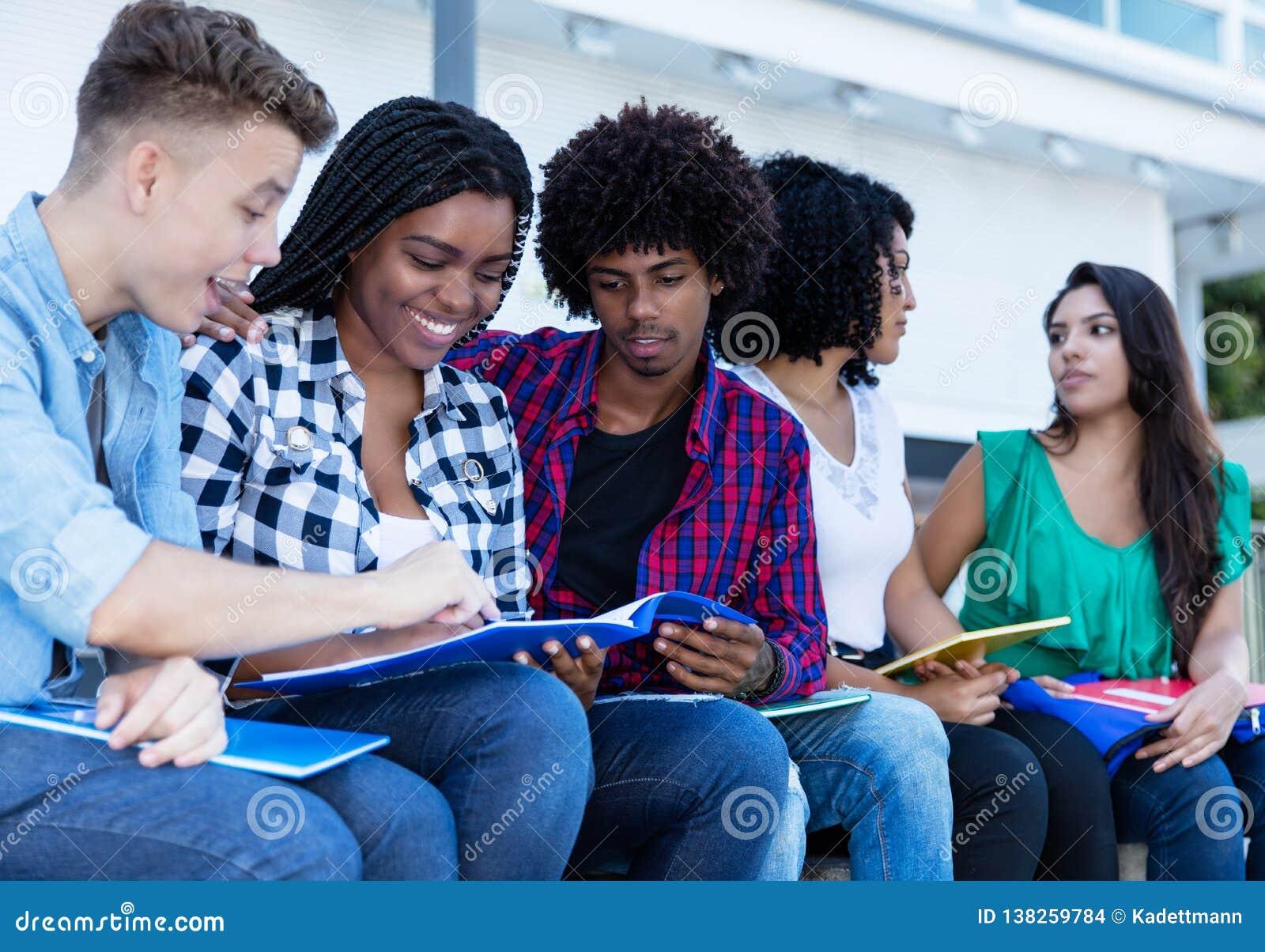 Gruppe internationale Studenten, die draußen auf dem Campus lernen